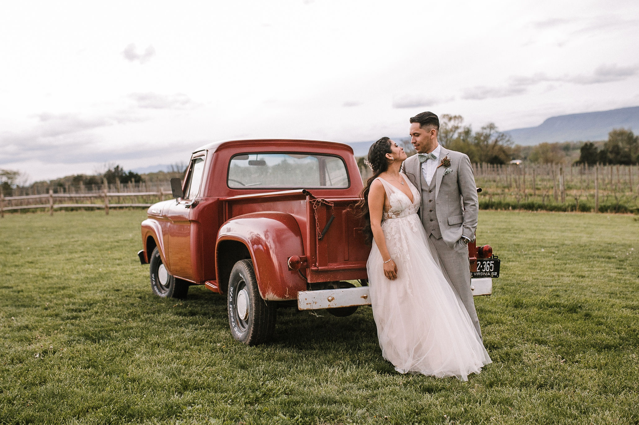 bride and groom smile as they lean against car at the Faithbrooke Barn & Vineyards
