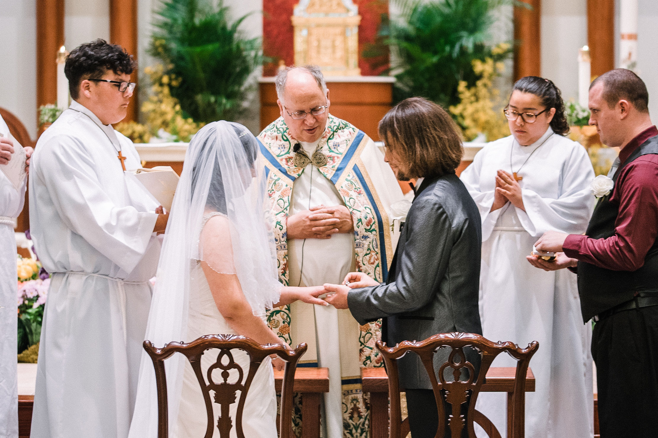 bride and groom exchanging rings at all saints catholic church