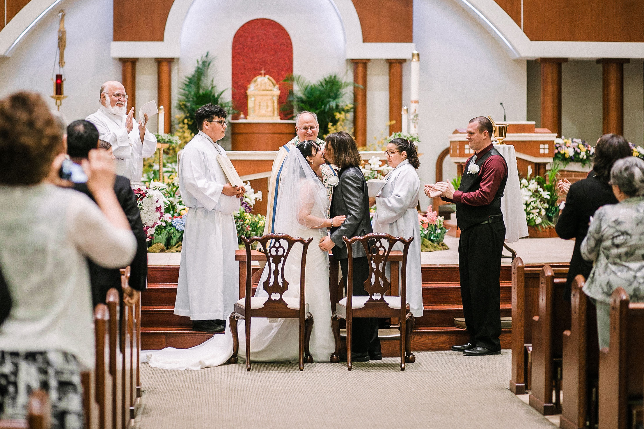 bride and groom kissing at altar at all saints catholic church