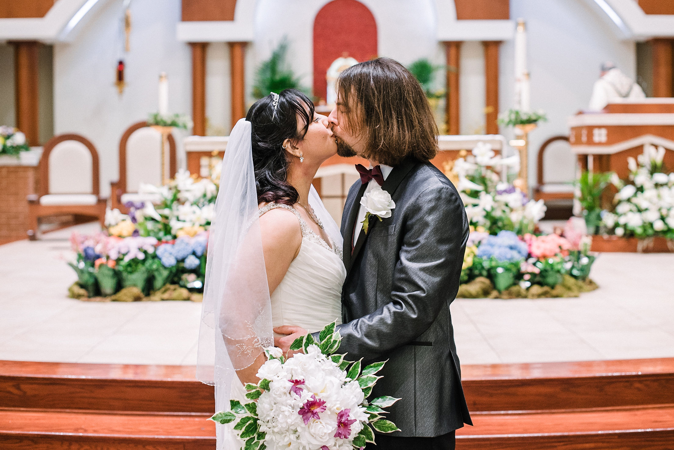 bride and groom kissing in church at all saints catholic church
