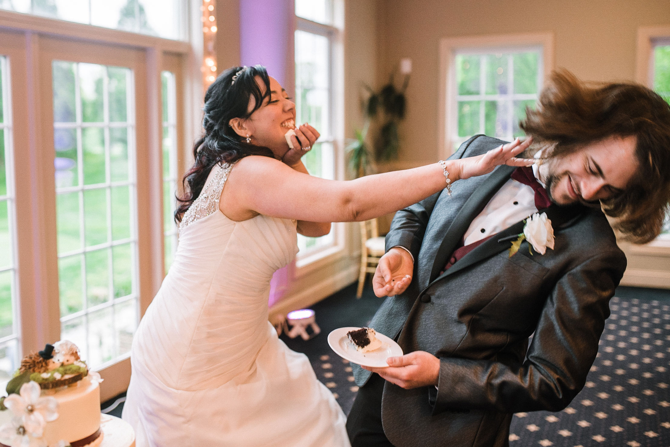 bride and groom cutting cake playfully at westfields golf club