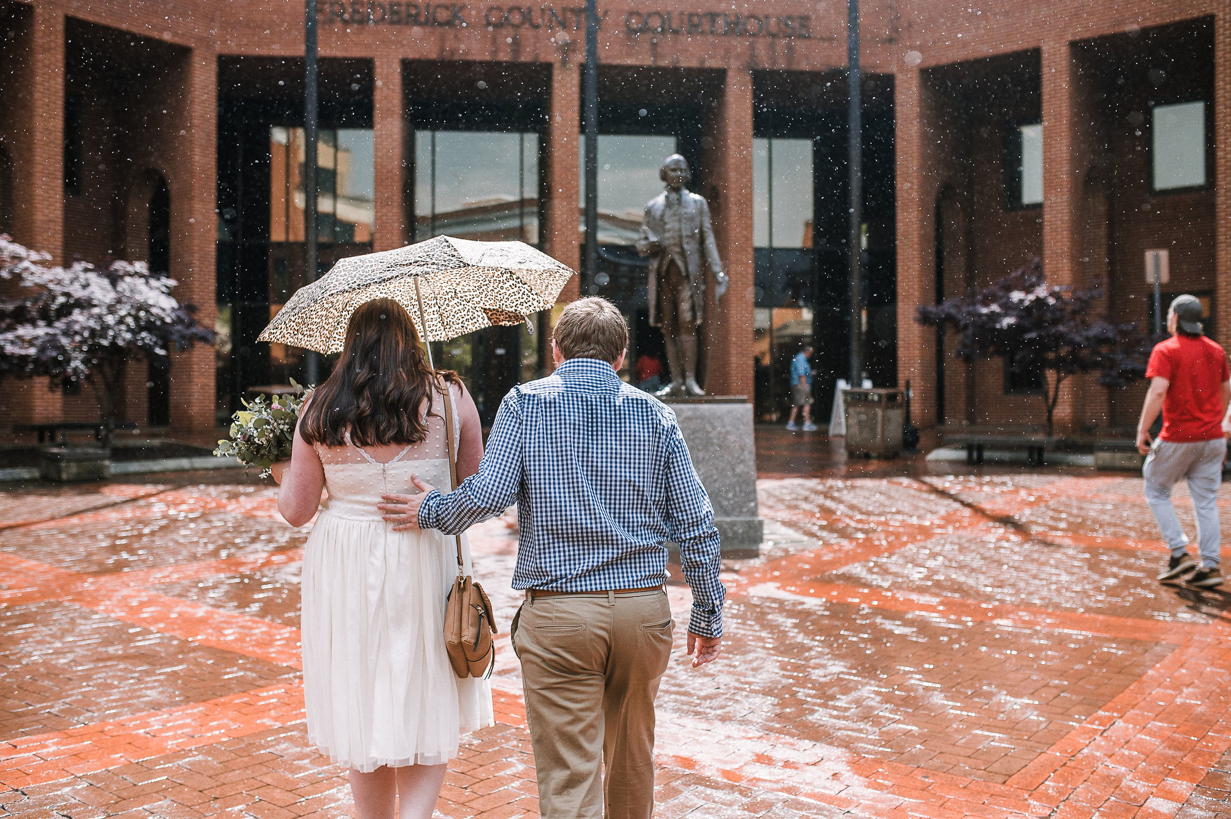 bride and groom walking into city hall in frederick, md