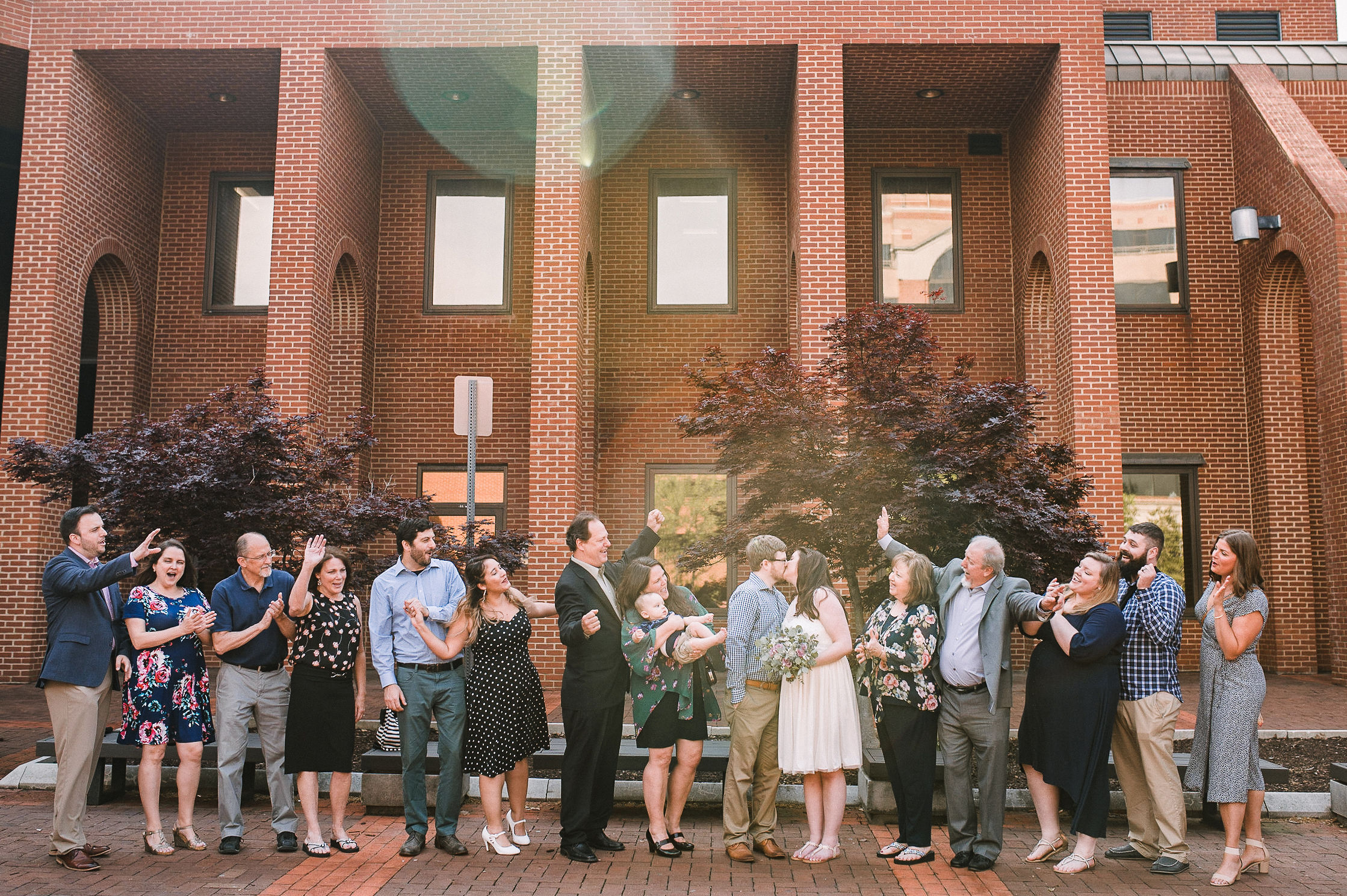 friends and family cheering as bride and groom kiss at City Hall in Frederick, MD
