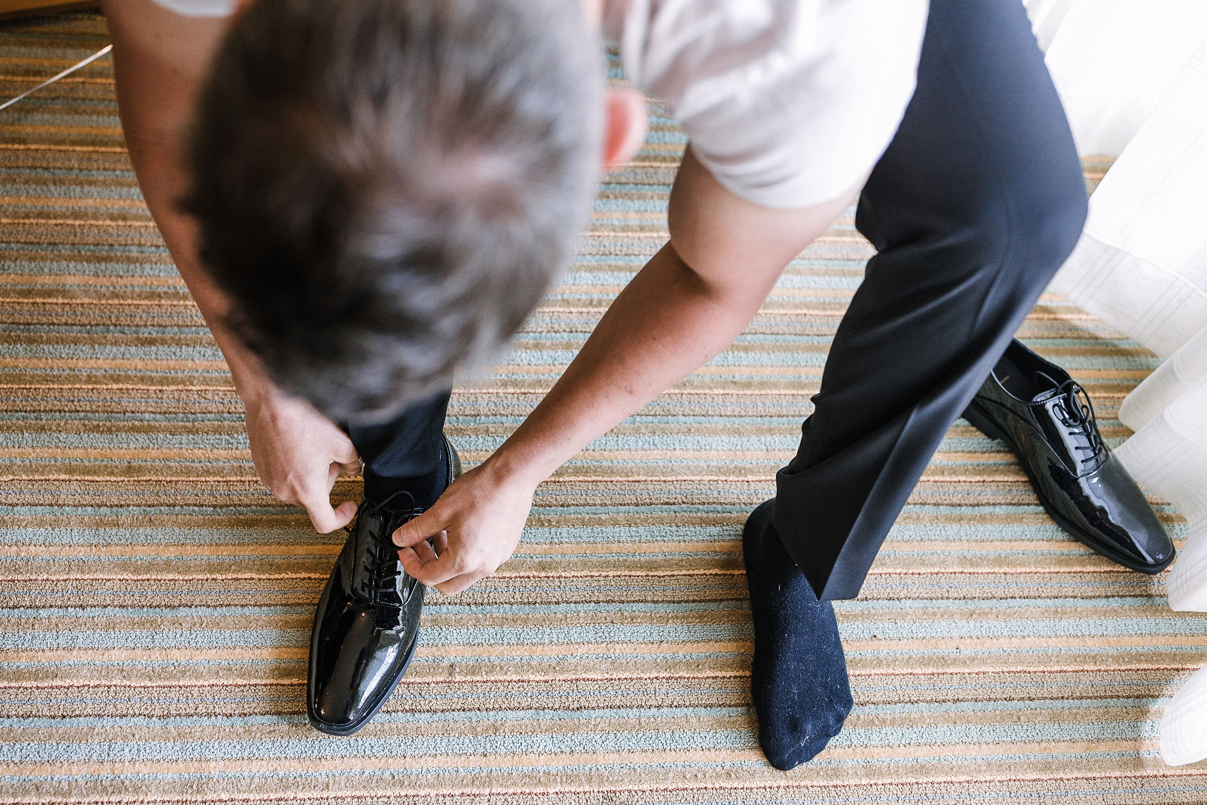 groom putting on shoes at The Salamander Resort
