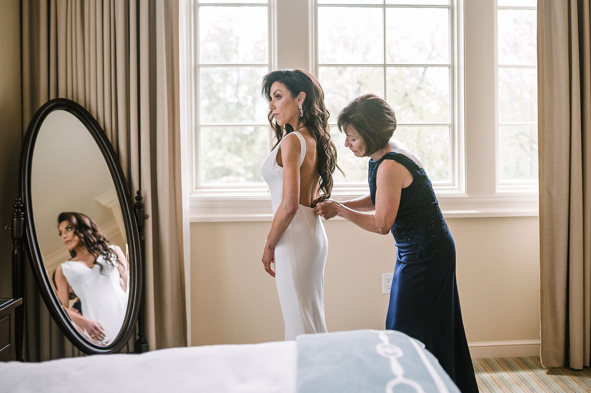 mother of the bride helping bride get into wedding dress at The Salamander Resort