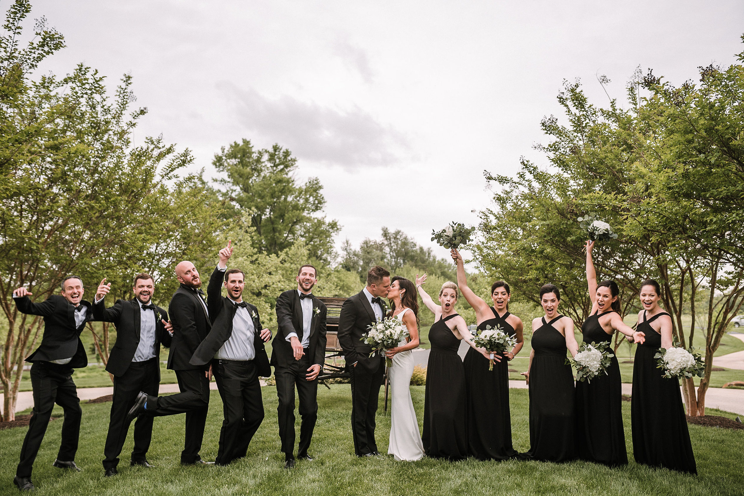 wedding party cheering as bride and groom kiss at The Salamander Resort