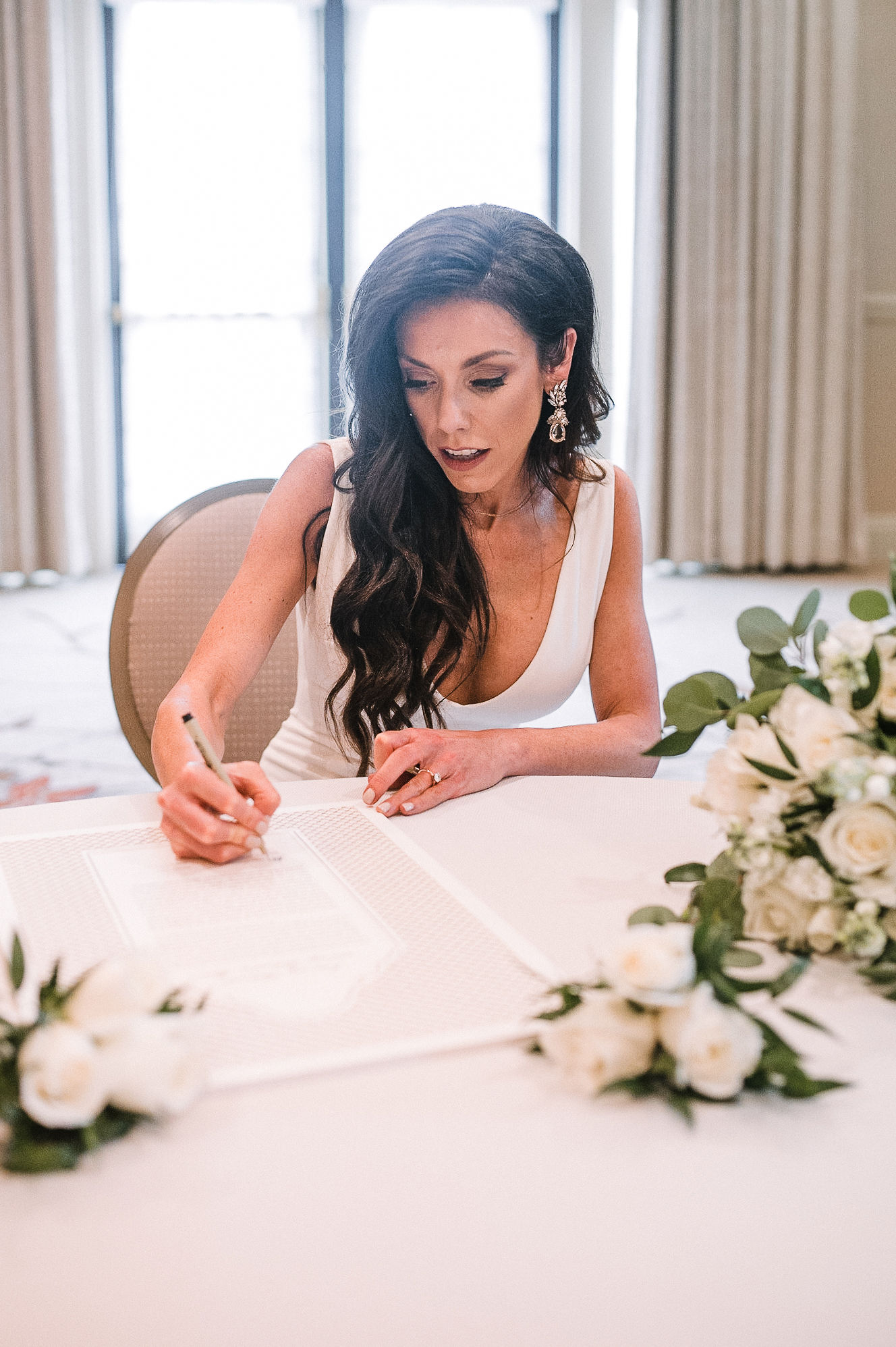 bride signing the ketubah at The Salamander Resort
