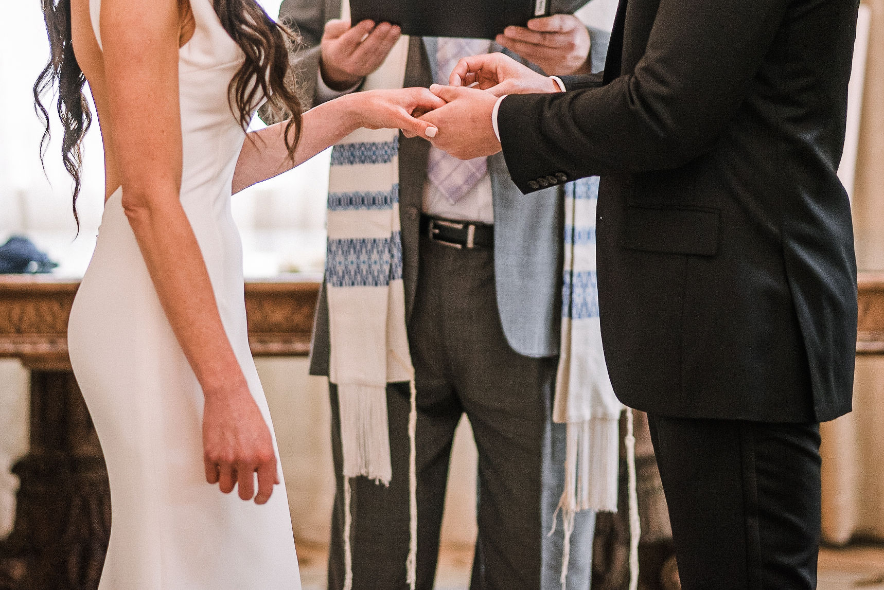 groom putting wedding ring on bride's finger at The Salamander Resort
