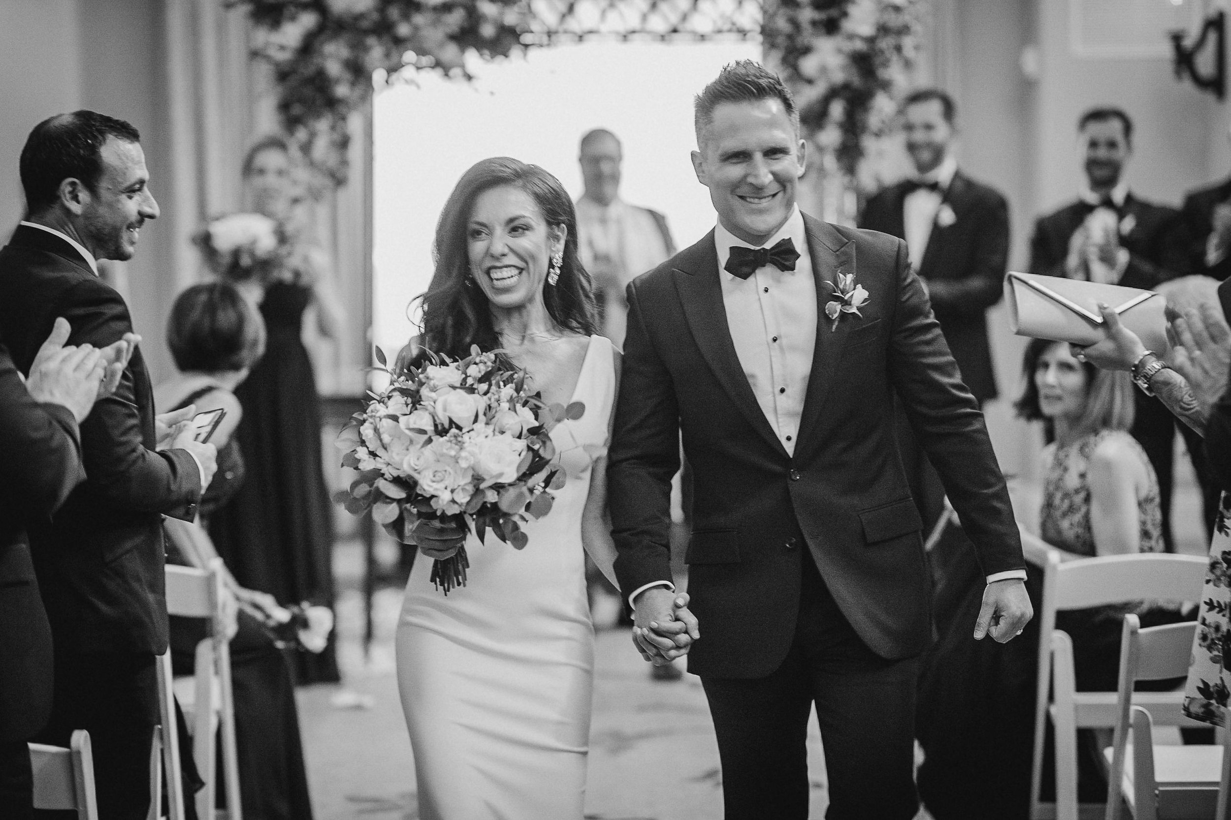 bride and groom smiling as they walk up the aisle at The Salamander Resort