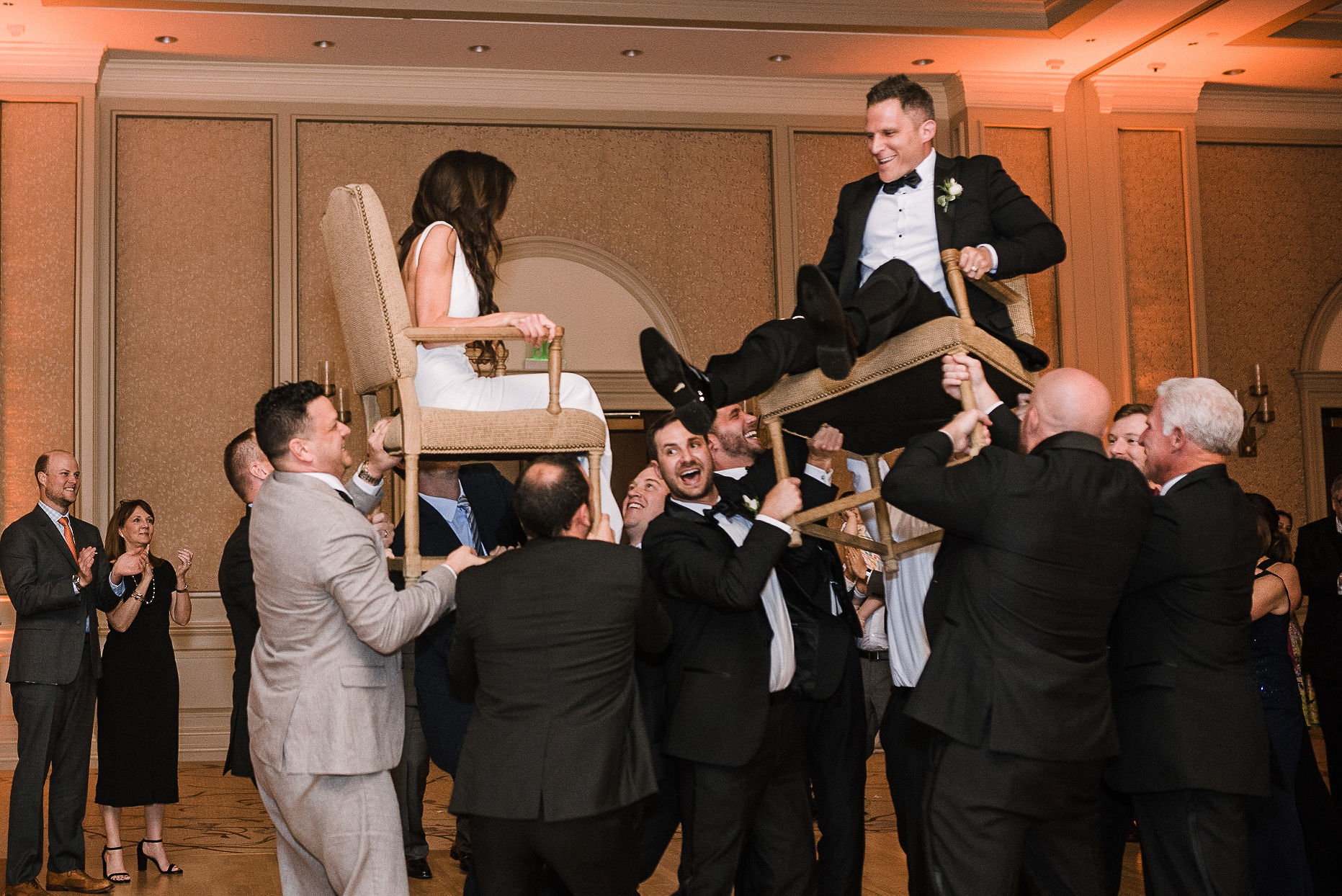 bride and groom sitting in chair and being carried by guests at The Salamander Resort