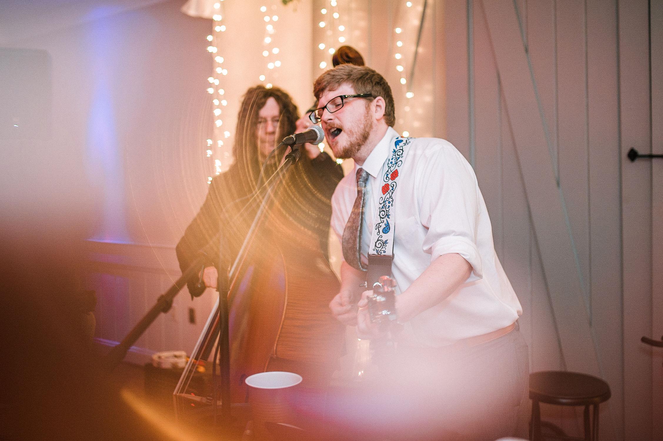 groom playing guitar at wedding reception at MAVFC Reception Hall