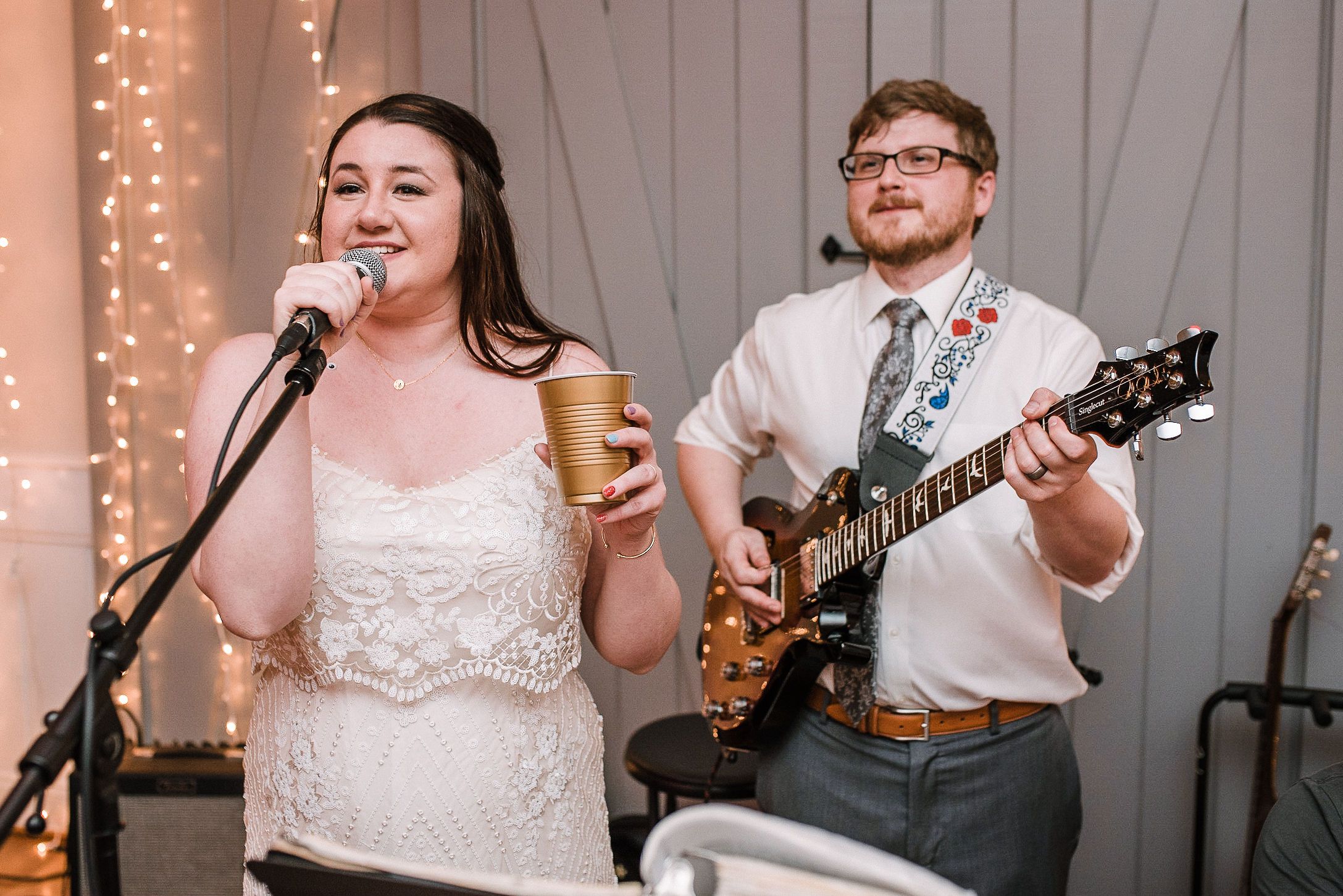 bride sings as groom plays guitar at wedding reception at MAVFC Reception Hall