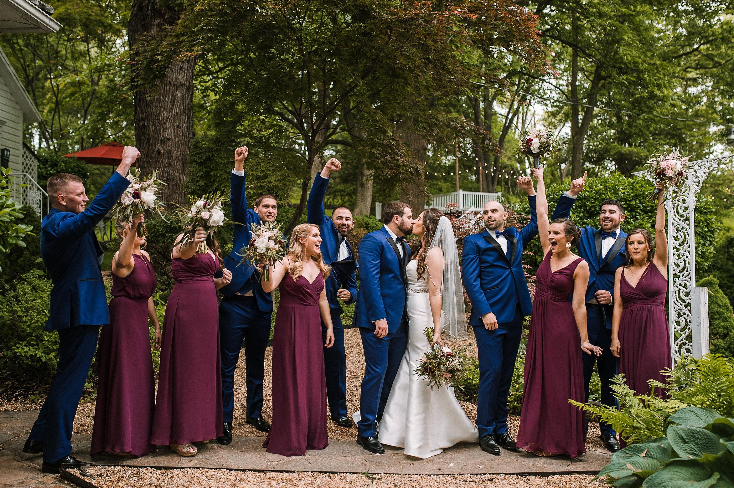 wedding party cheering as bride and groom kiss at Seasons at Magnolia Manor