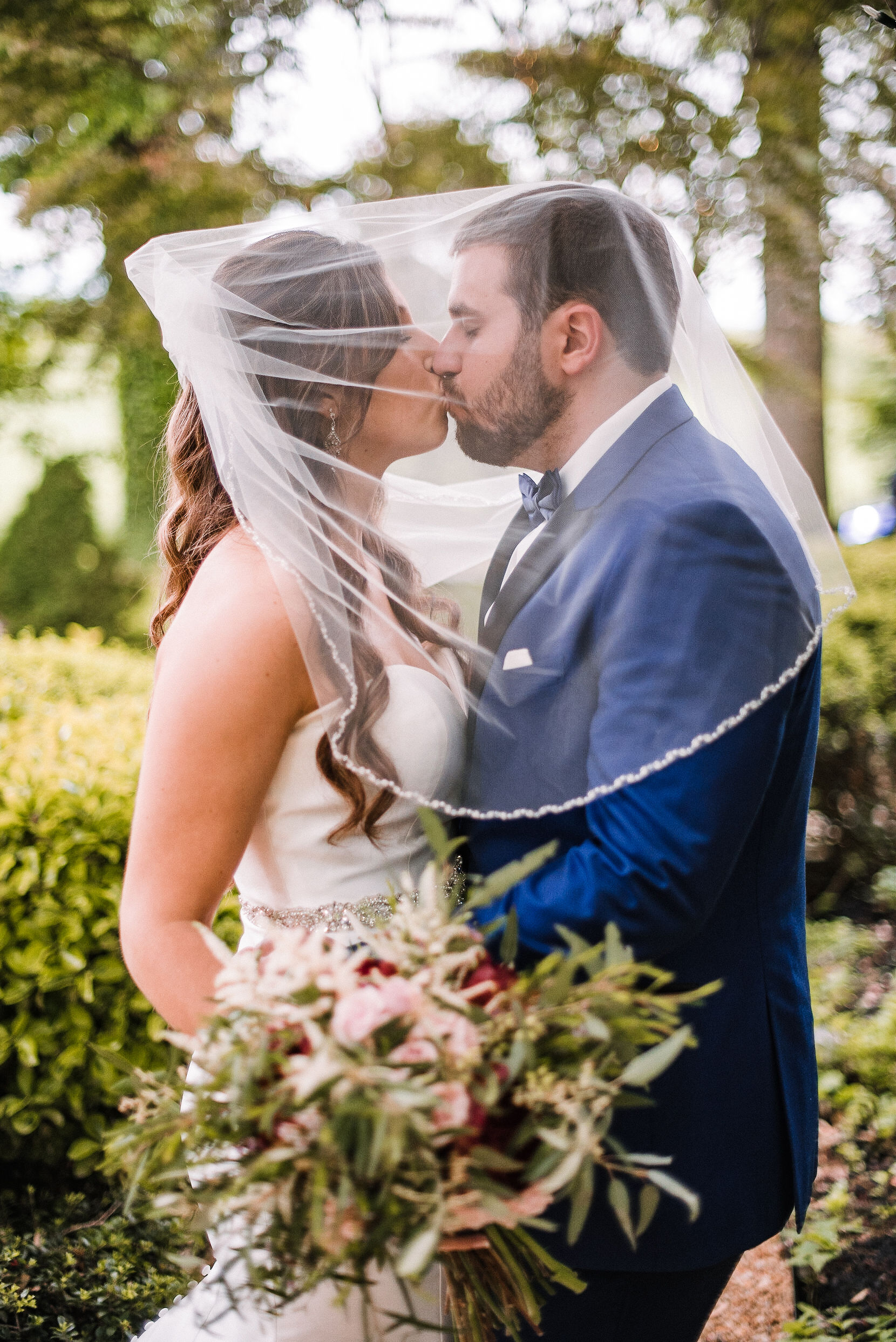 bride and groom kissing under veil at Seasons at Magnolia Manor