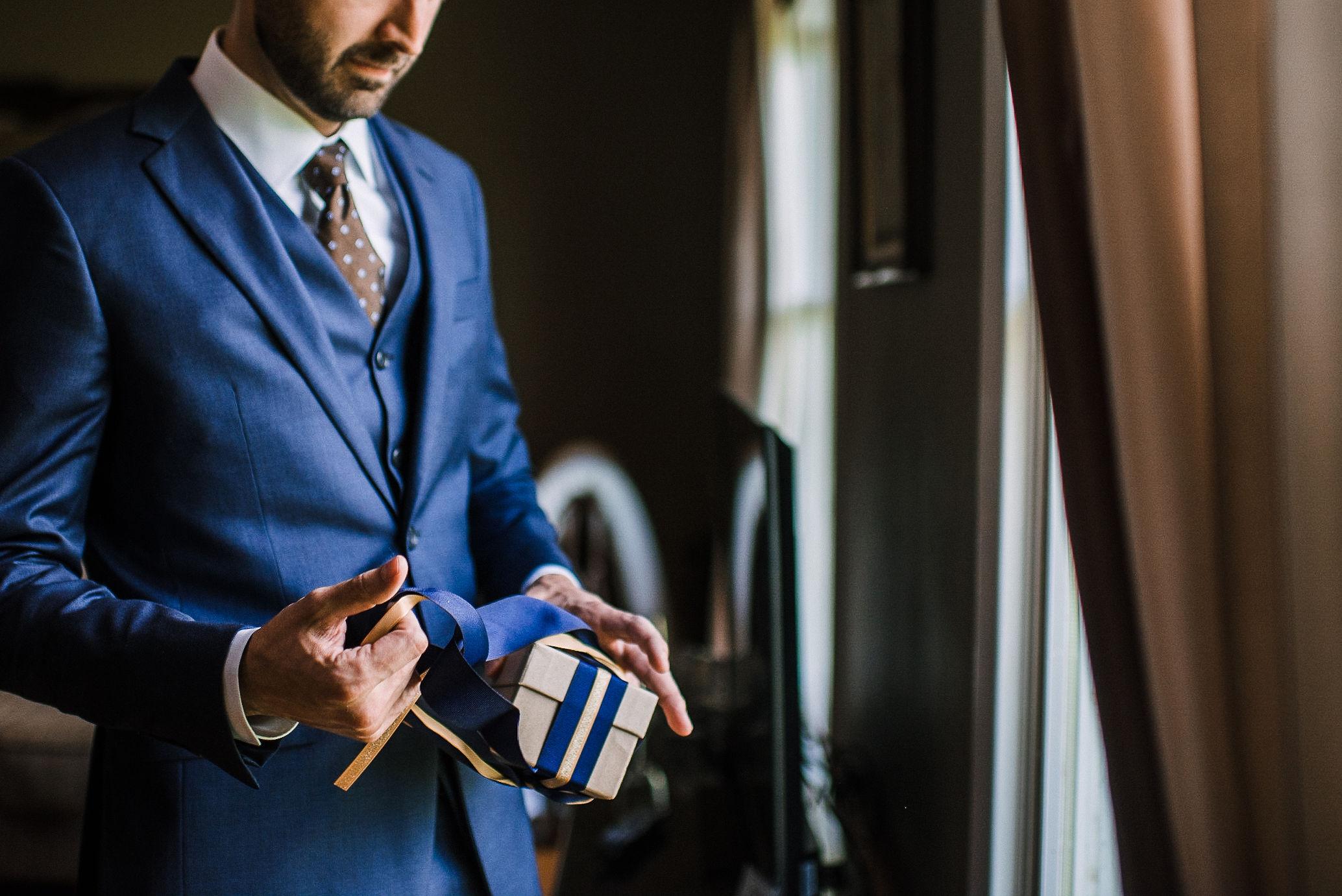 groom opening gift from bride at House Mountain Inn & Irvine Estate