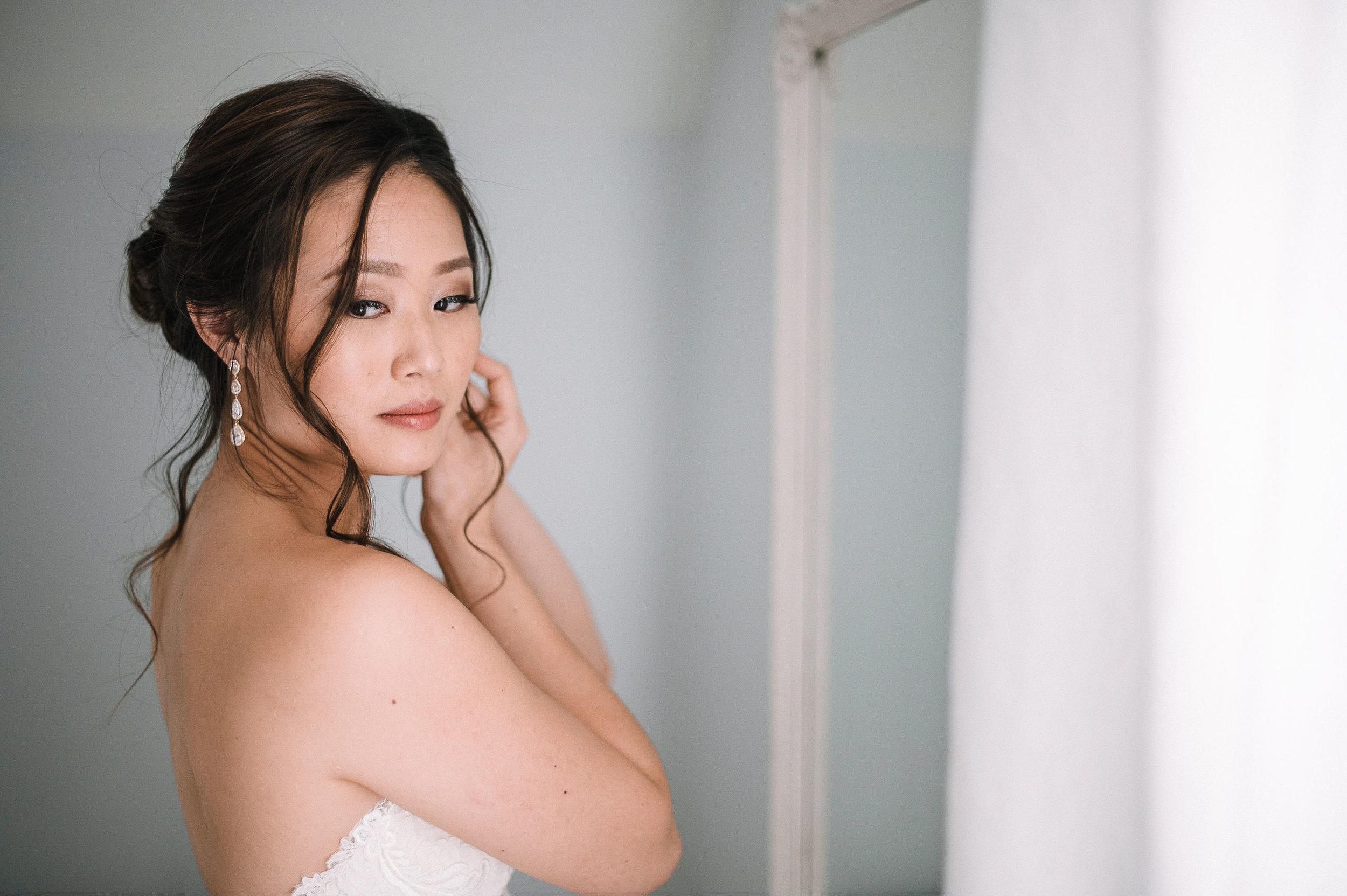 bride putting on earrings at House Mountain Inn & Irvine Estate
