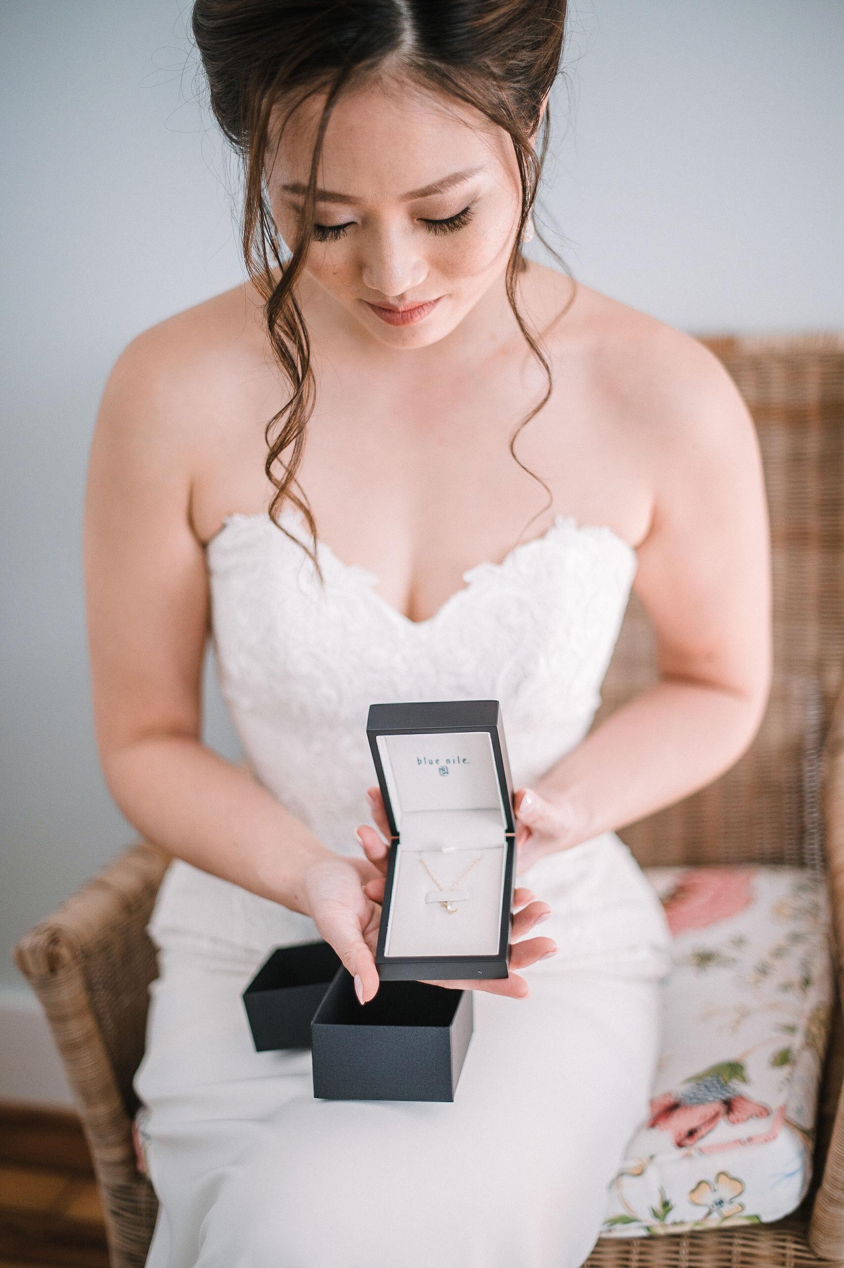 bride opening gift from groom at House Mountain Inn & Irvine Estate