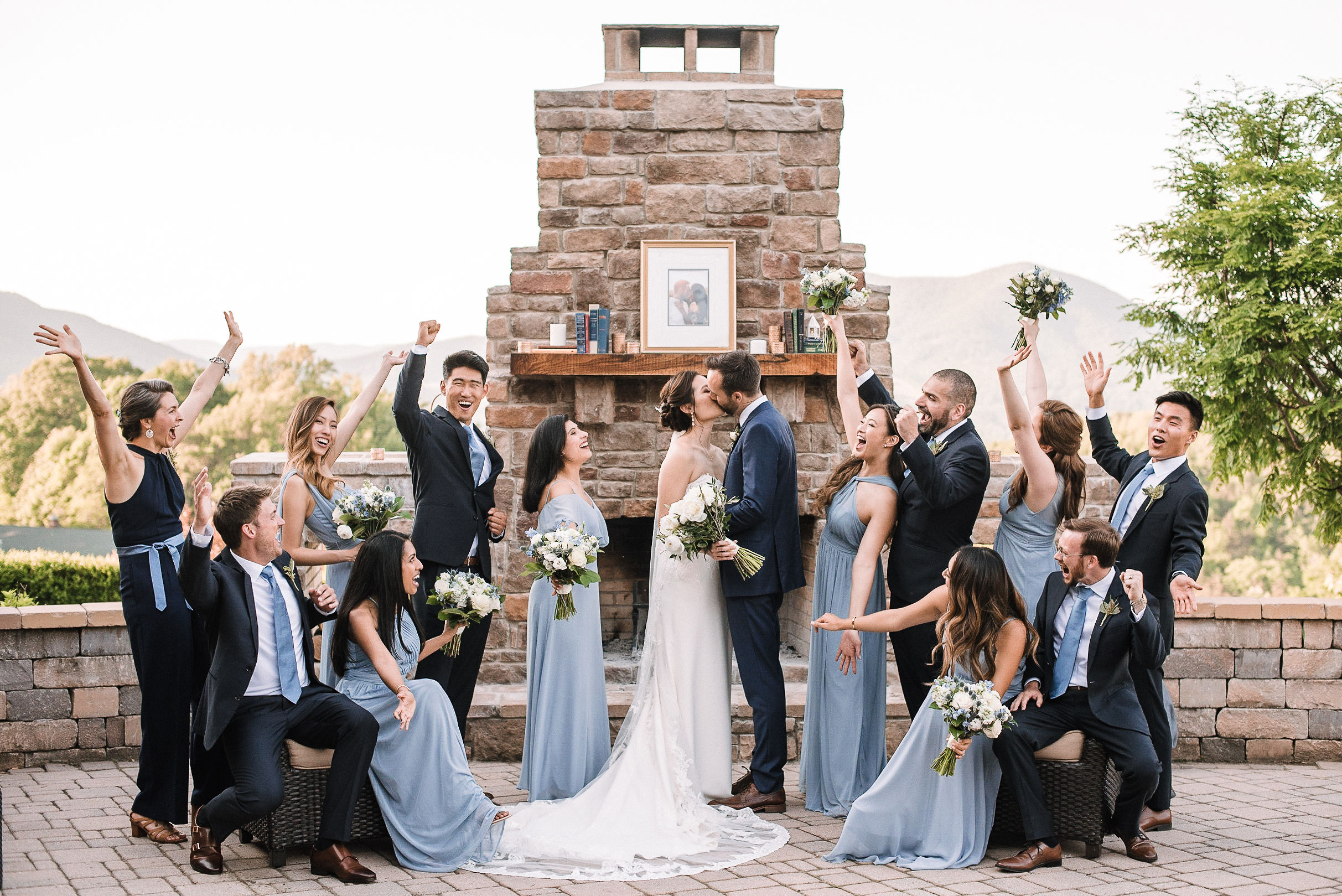 wedding party cheering as bride & groom kiss at House Mountain Inn & Irvine Estate