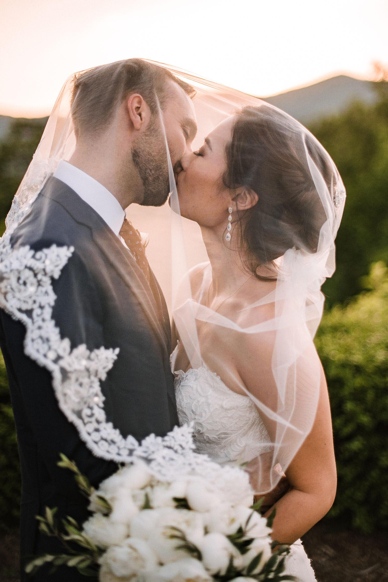 bride and groom kissing under veil at House Mountain Inn & Irvine Estate