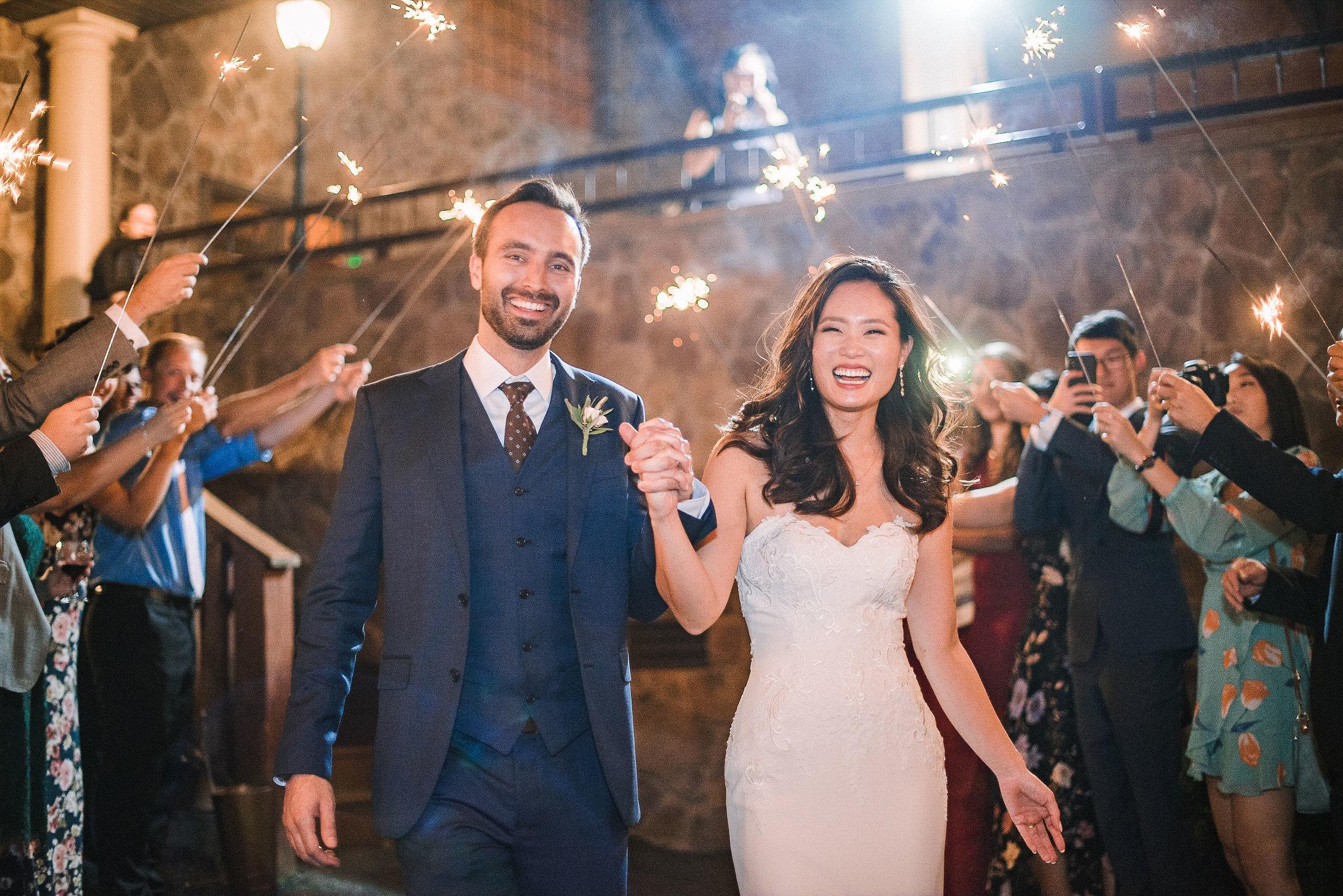 bride and groom smiling under sparkler exit at House Mountain Inn & Irvine Estate