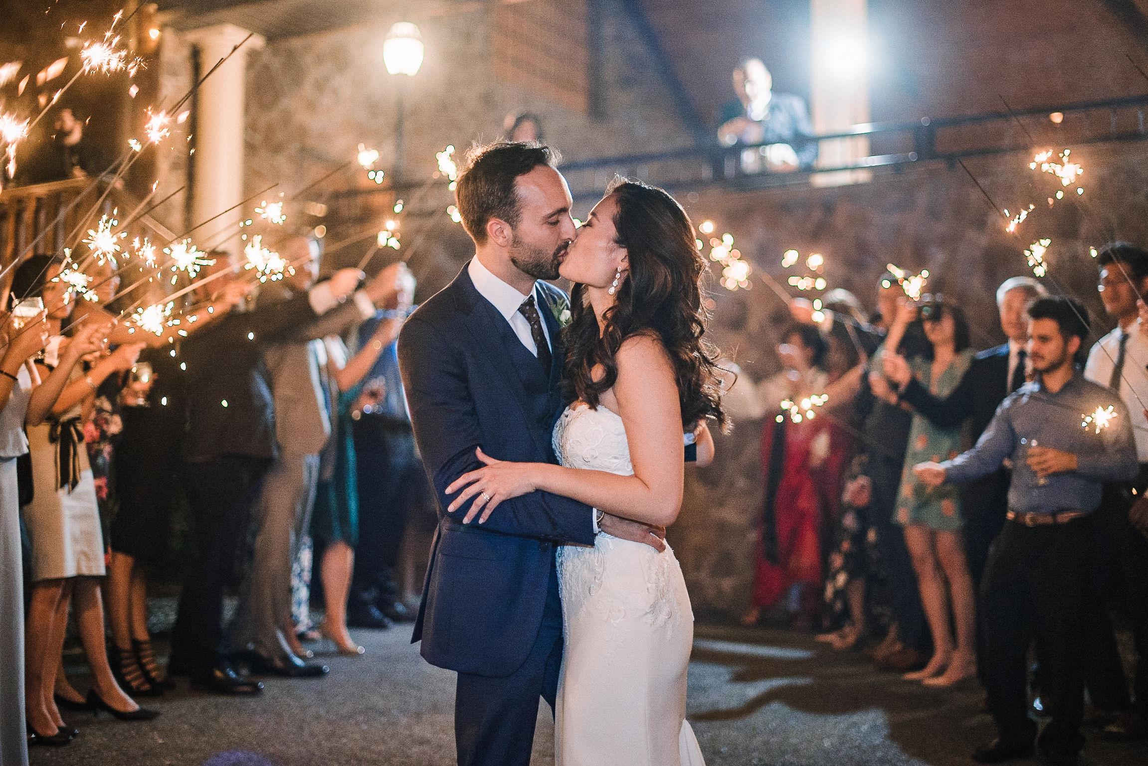 bride and groom kissing under sparkler exit at House Mountain Inn & Irvine Estate