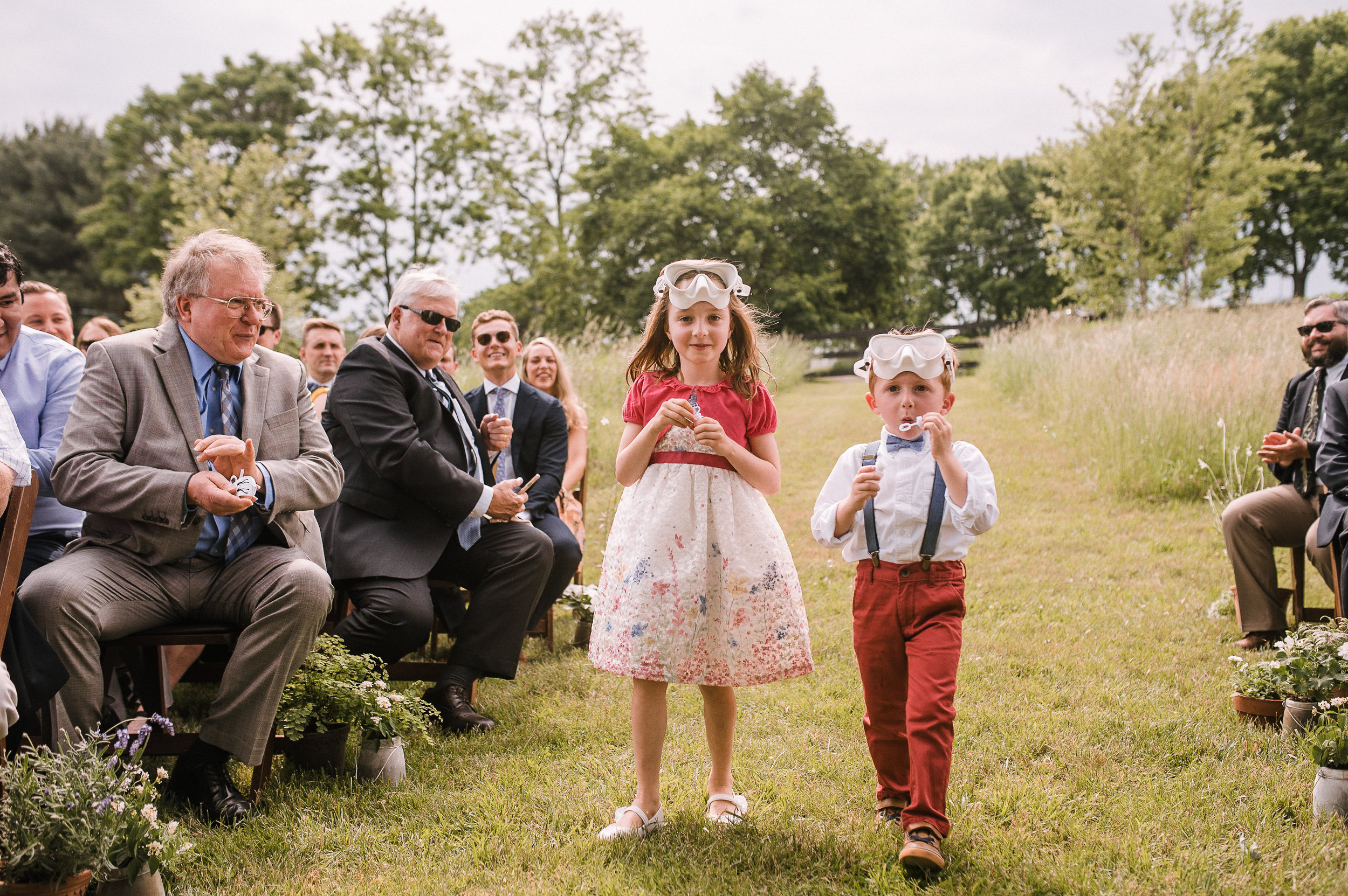 flower girl and boy coming down the aisle at tranquility farm