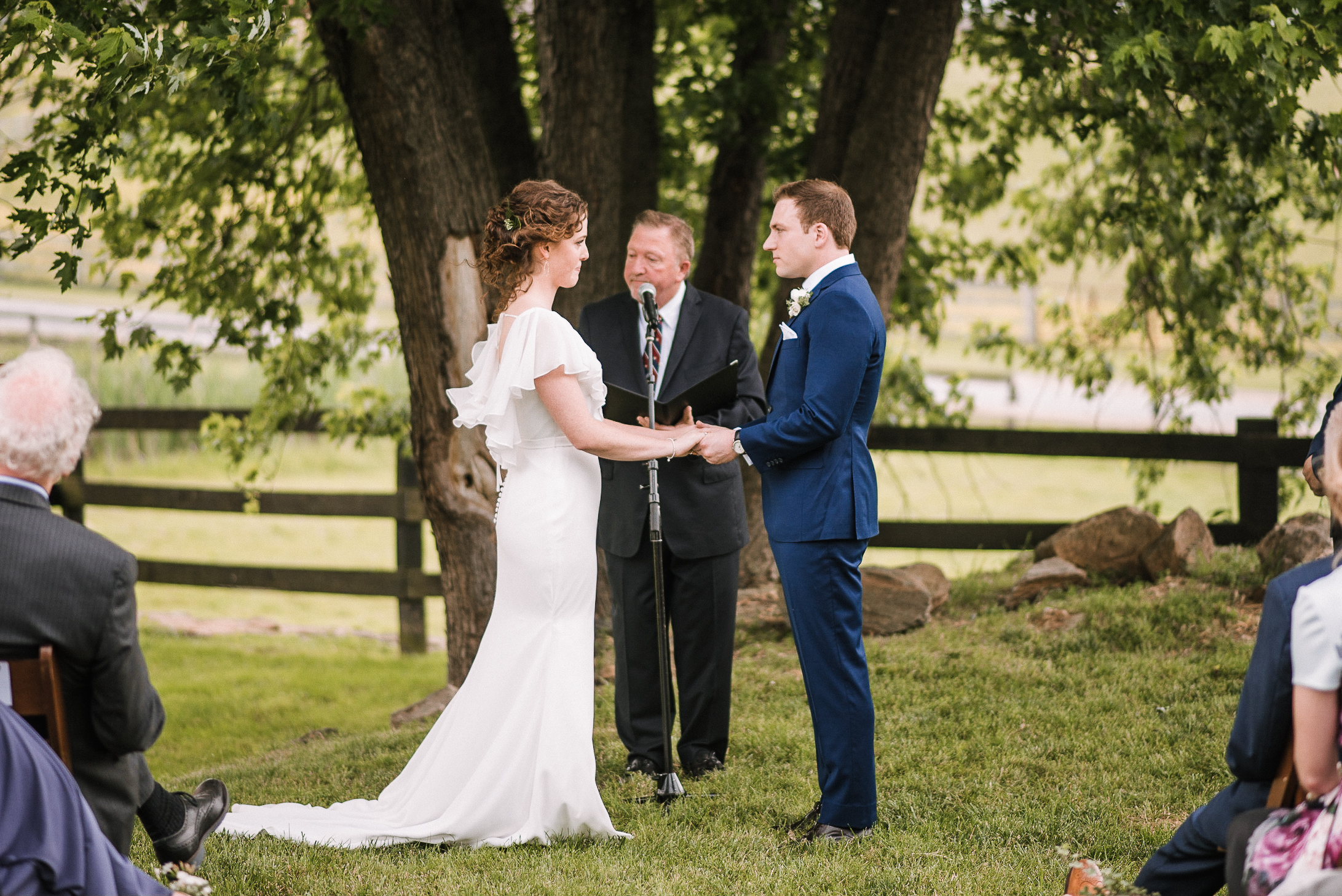 bride and groom holding hands at ceremony at tranquility farm