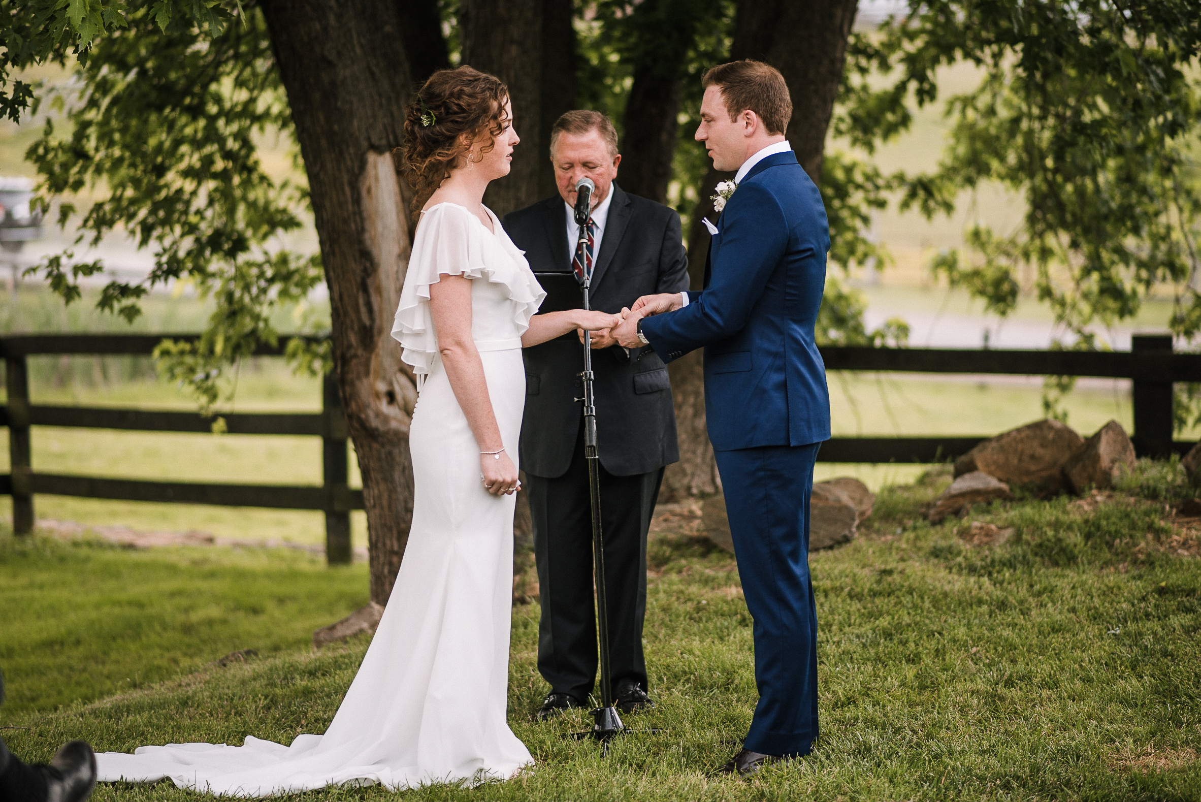 bride and groom exchanging rings at tranquility farm