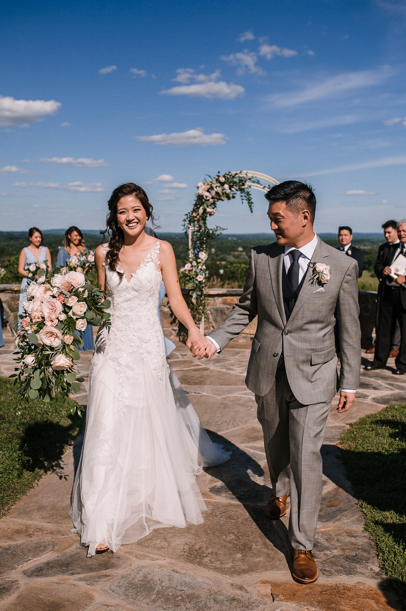 bride and groom holding hands coming up the aisle at Bluemont Vineyard