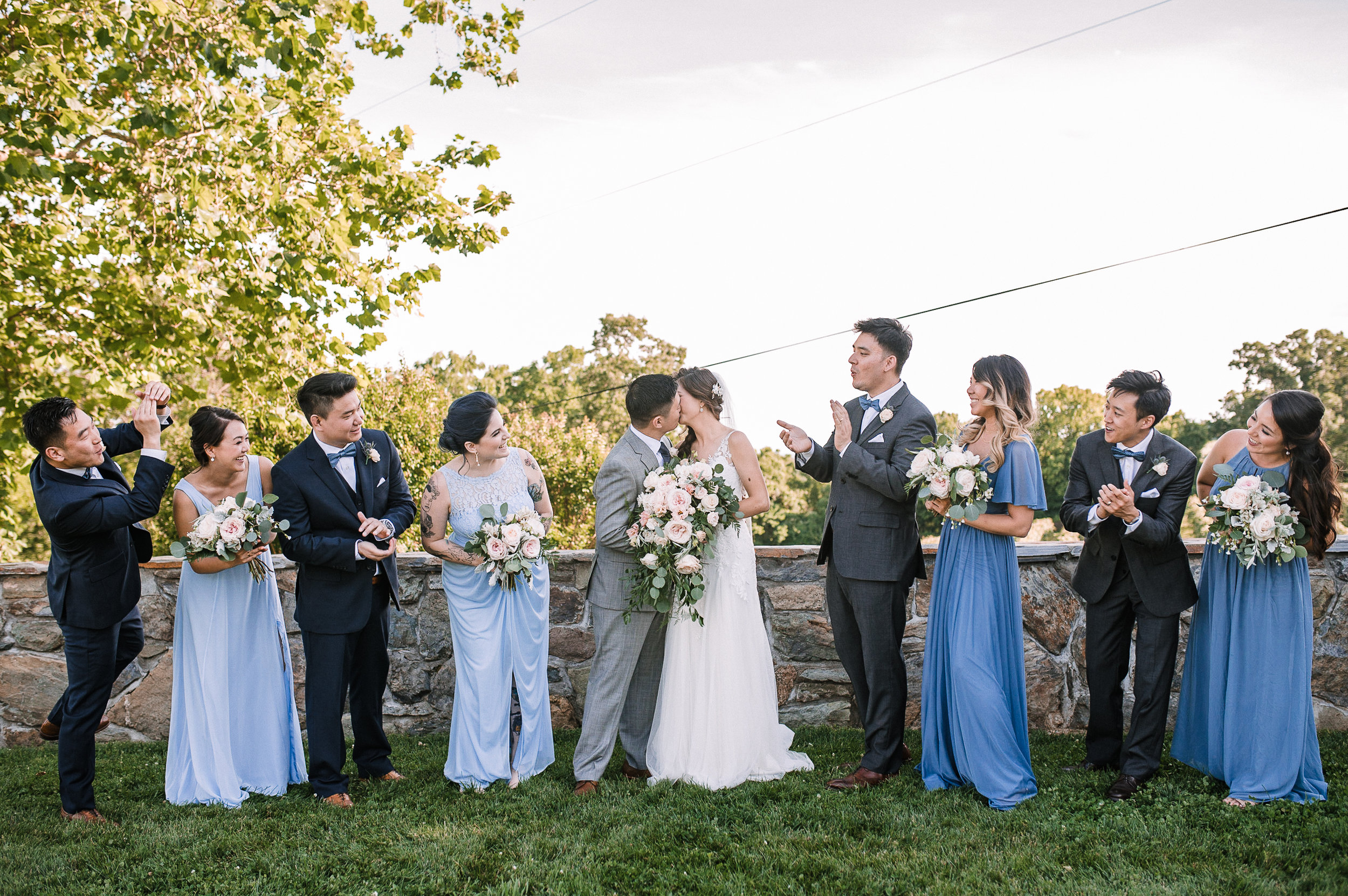 bride and groom kissing and wedding party cheers at Bluemont Vineyard