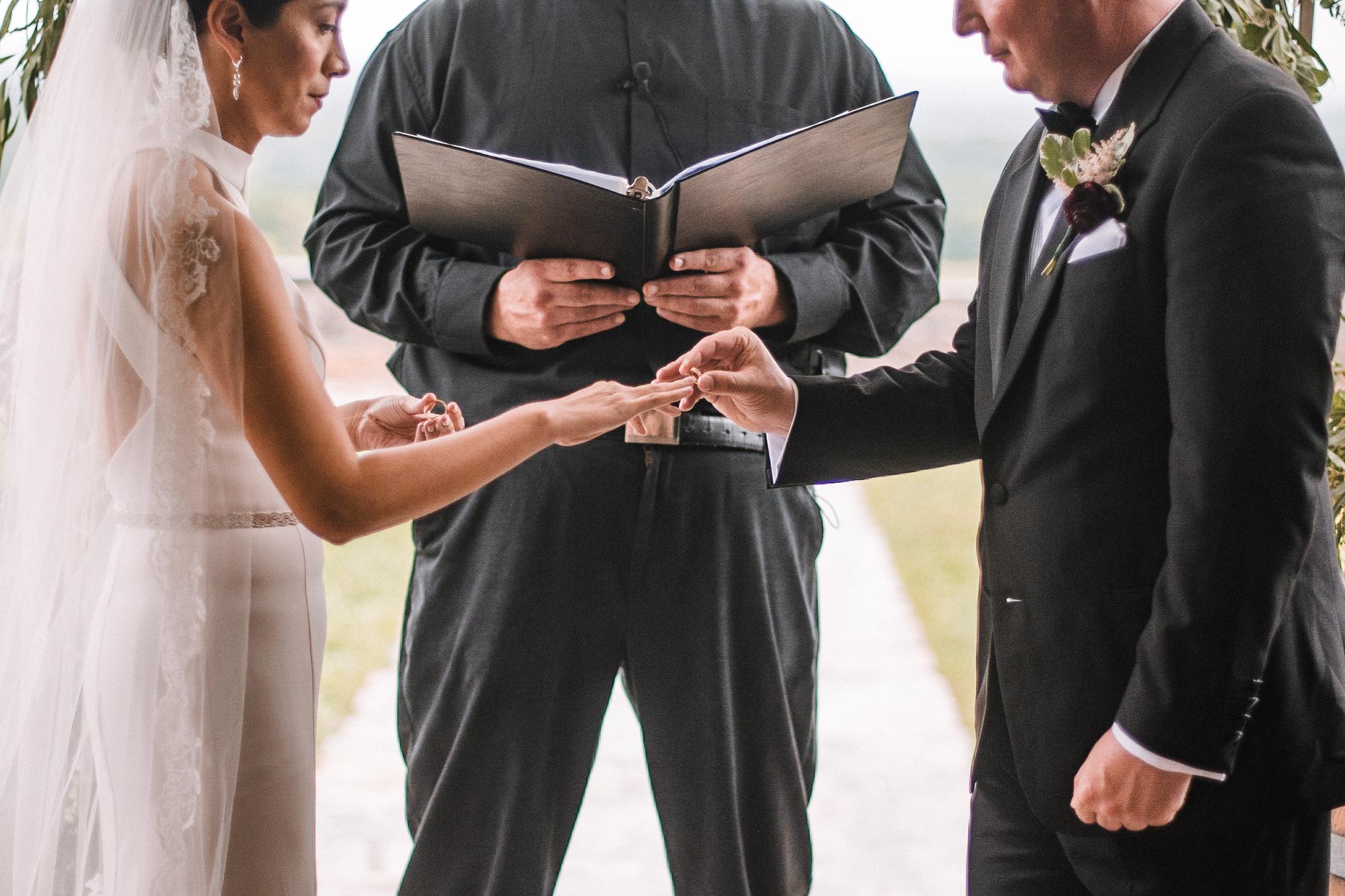 bride and groom exchanging wedding rings at Bluemont Vineyard