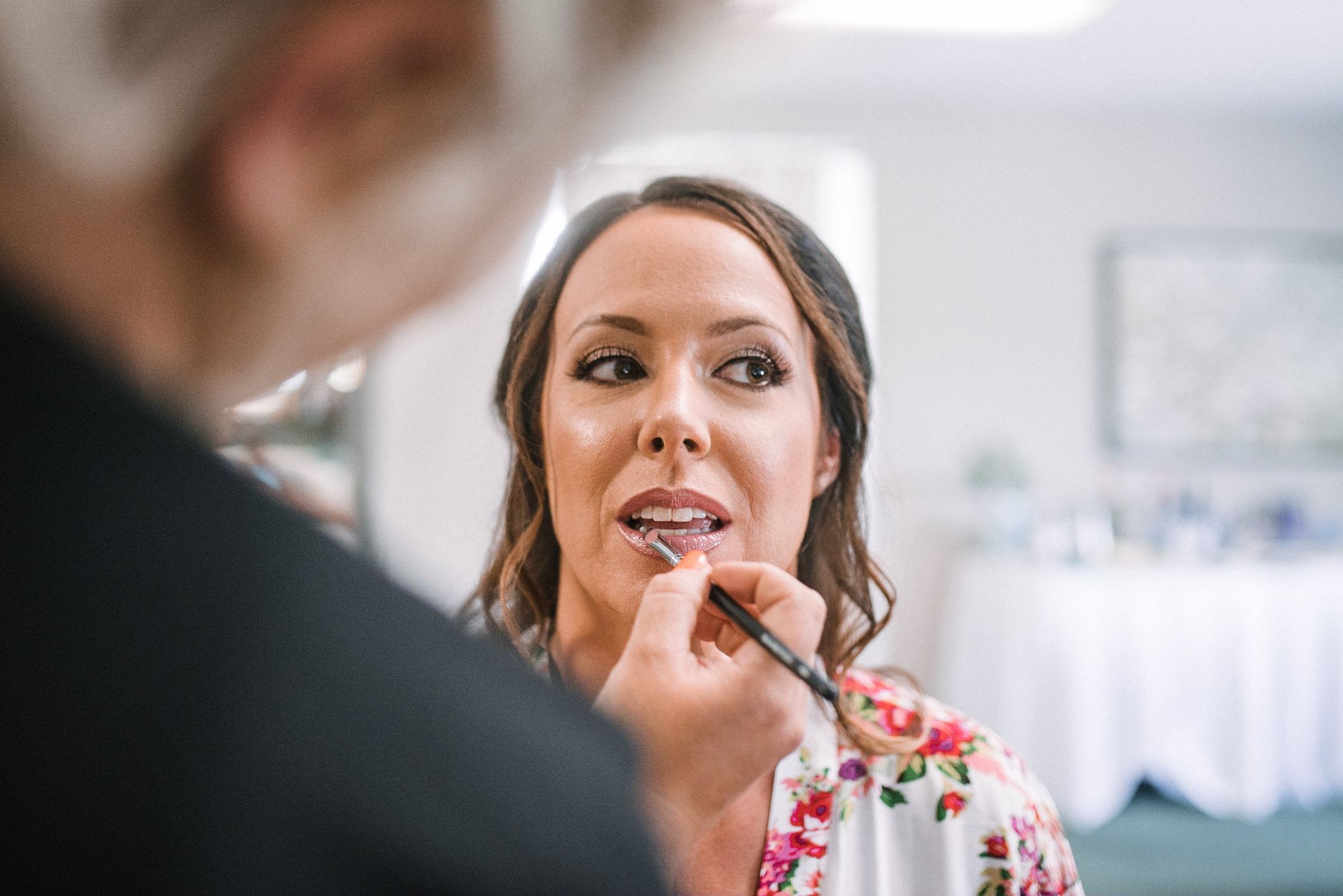 bride getting her makeup done at Evergreen Country Club
