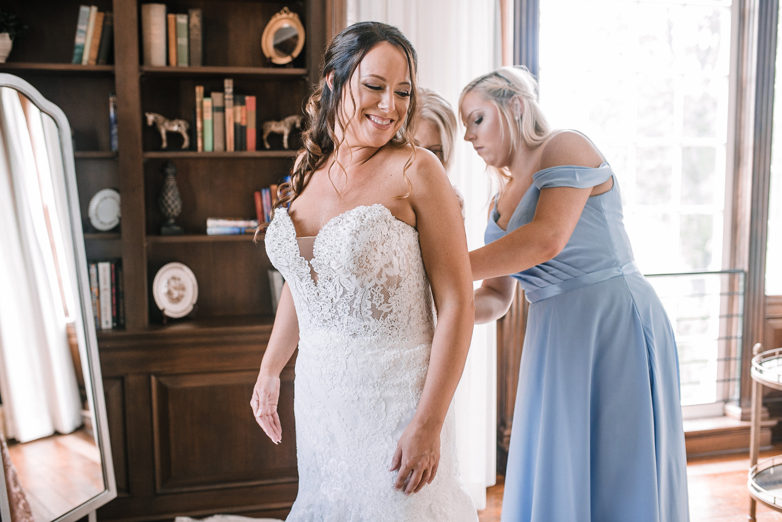 bride getting into wedding dress at Evergreen Country Club