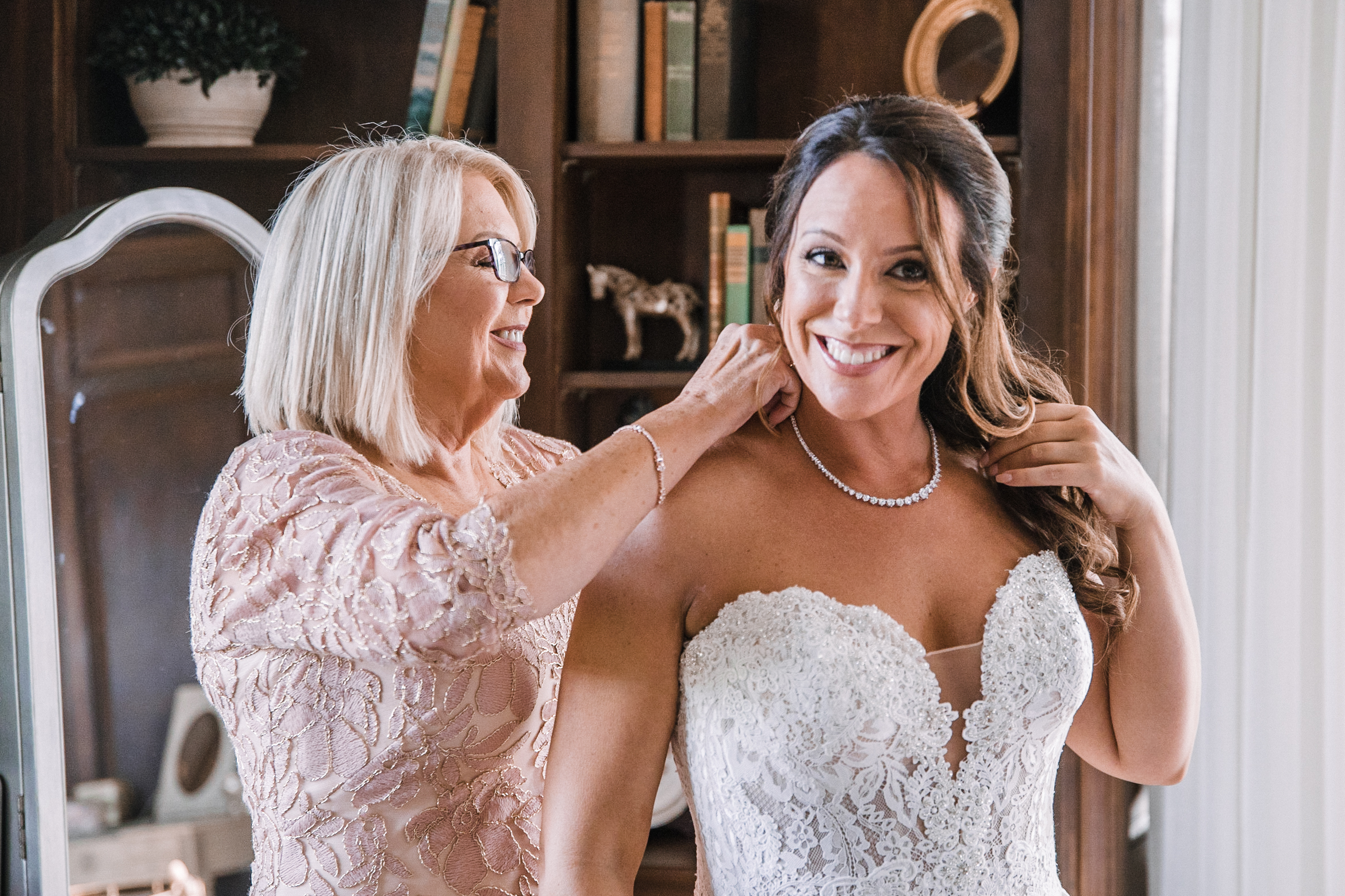mother of the bride putting necklace on bride at Evergreen Country Club