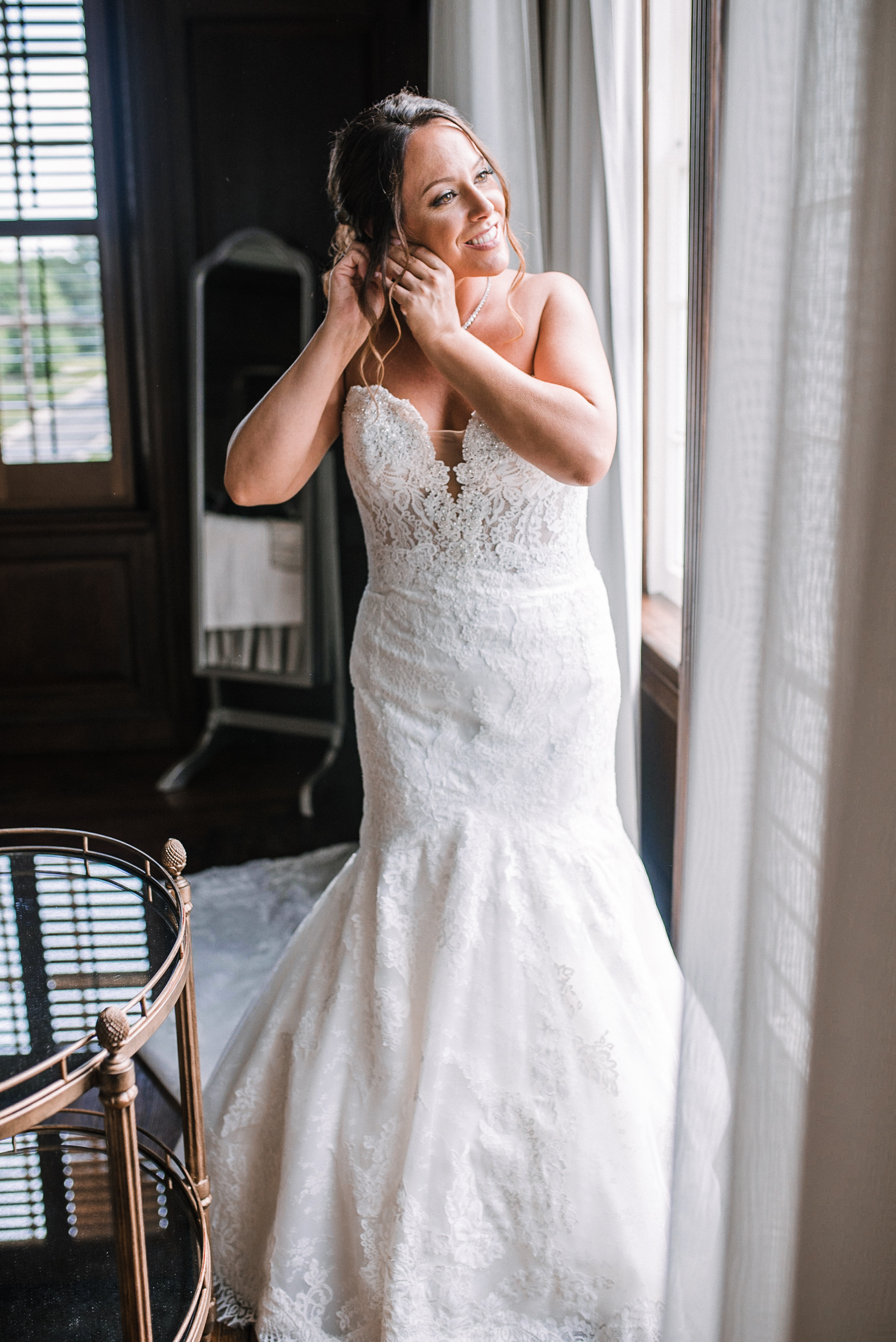 bride putting on earrings at Evergreen Country Club