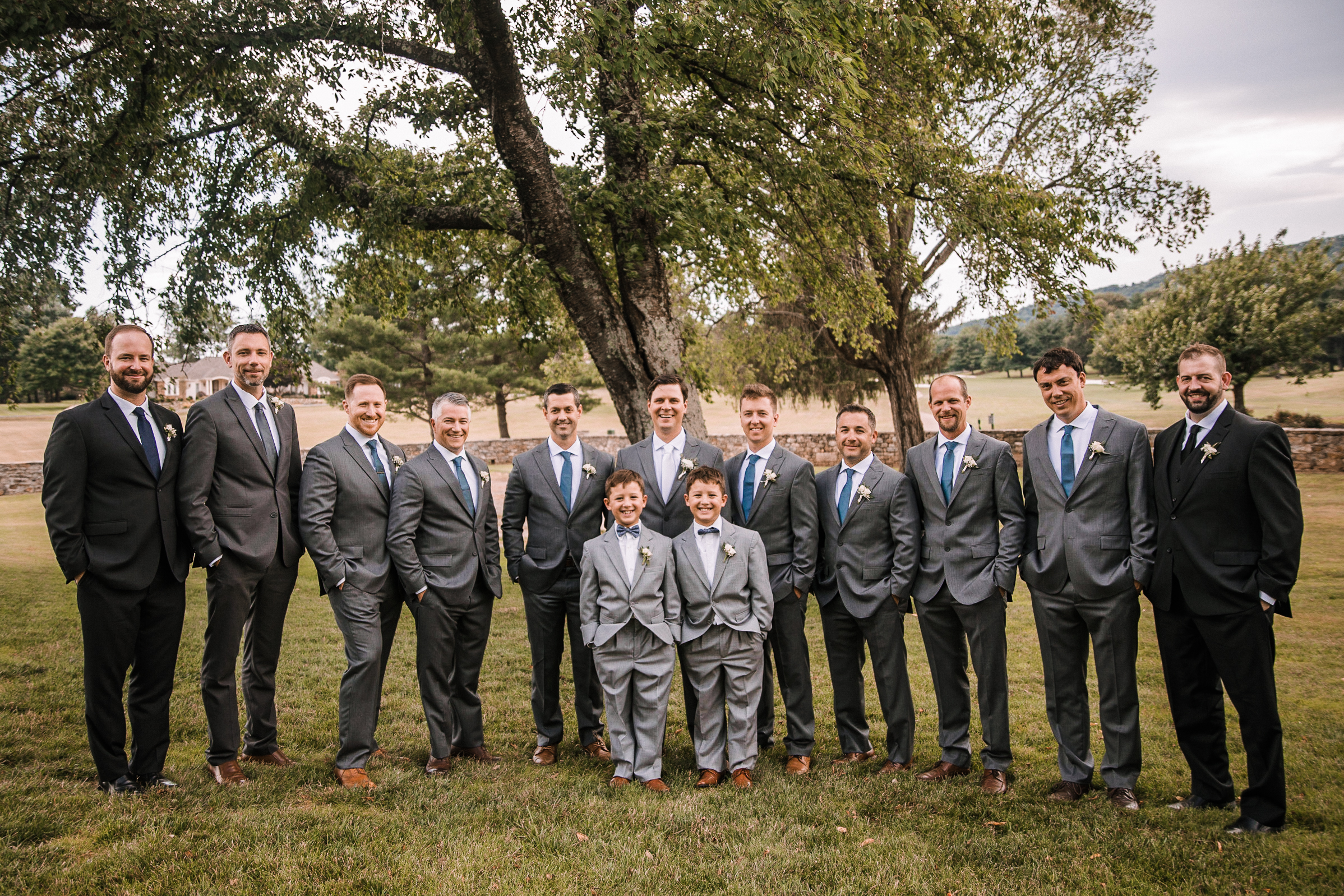 groom and groomsmen smiling at Evergreen Country Club