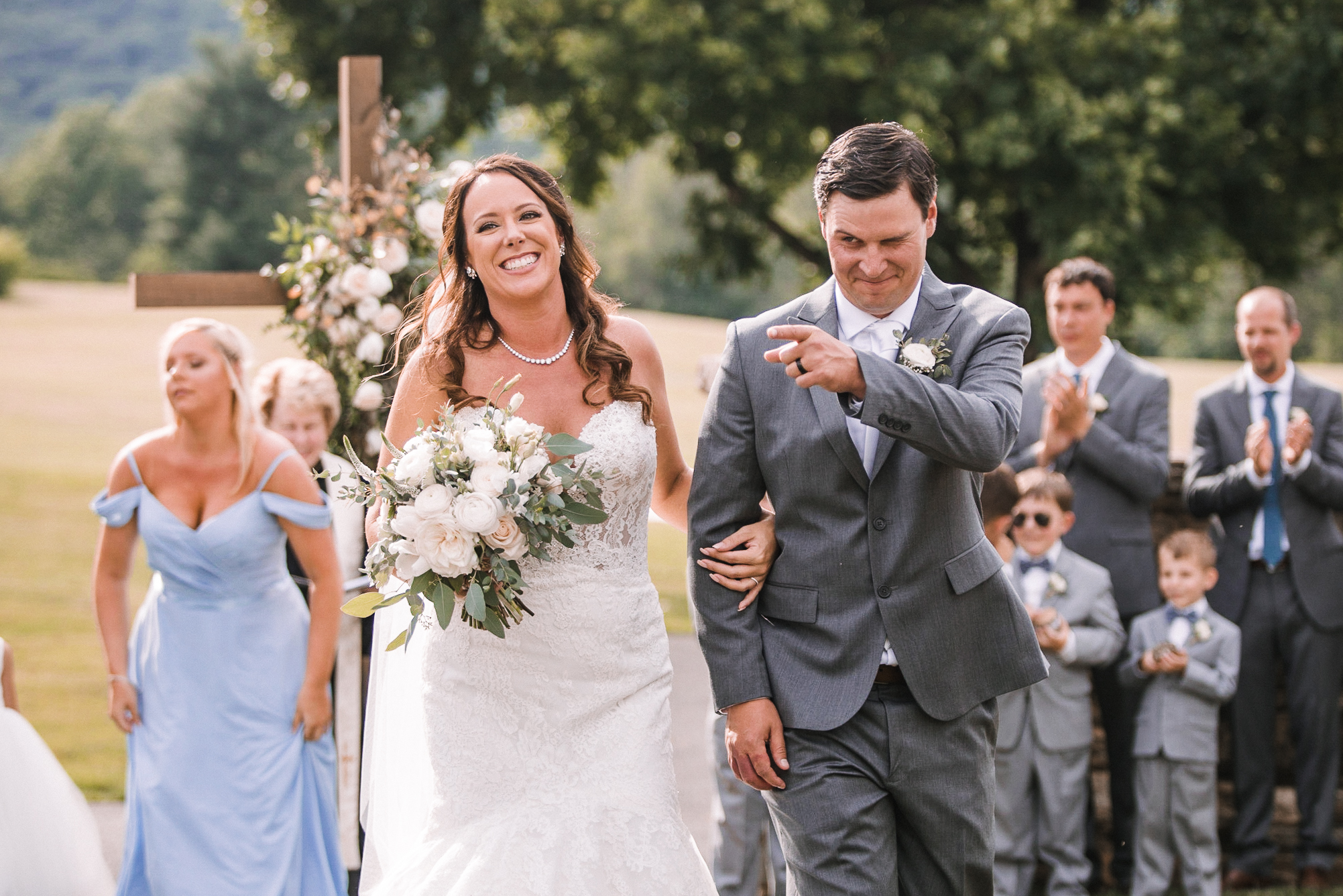 bride and groom smiling as they leave ceremony at Evergreen Country Club