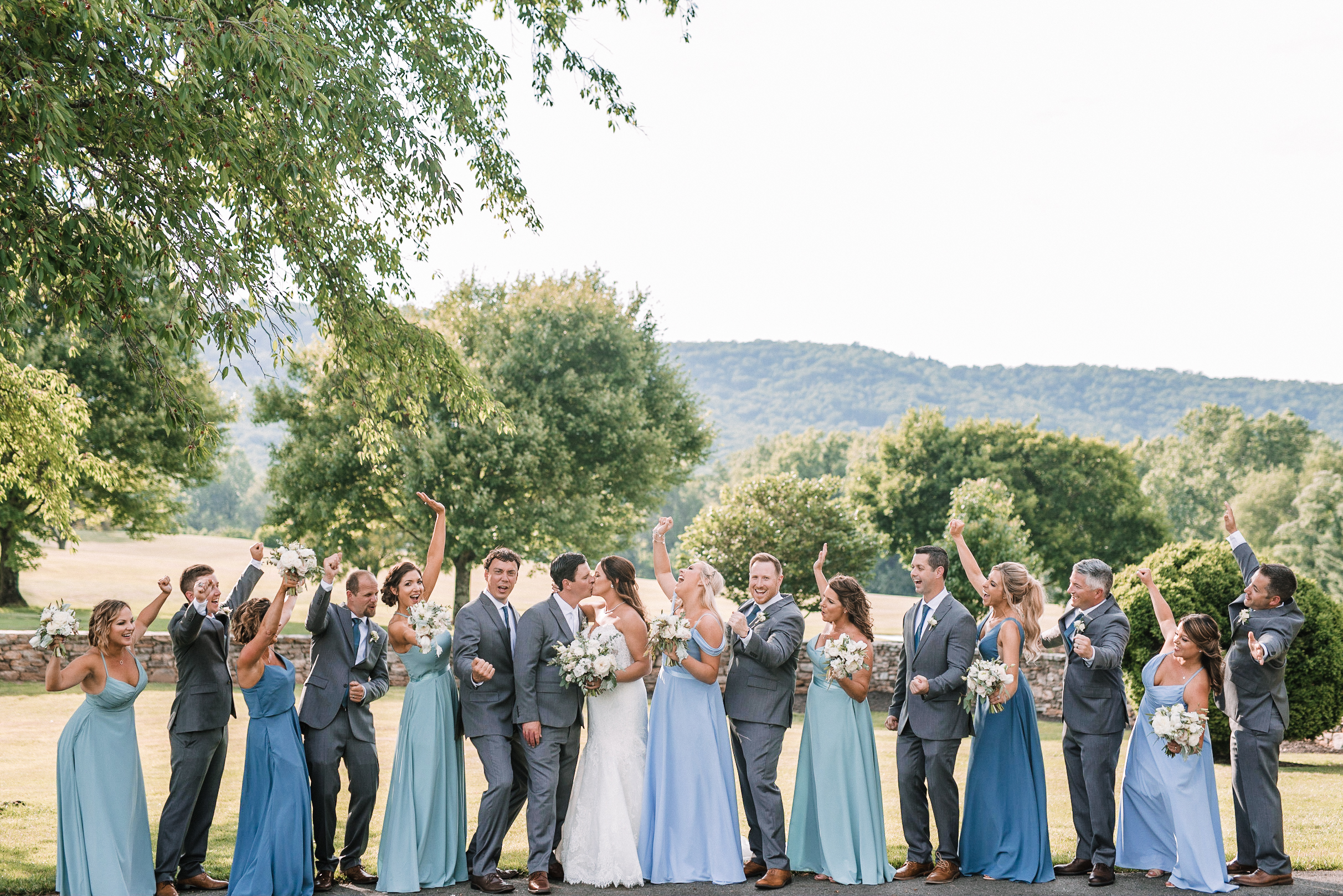 wedding party cheering as bride and groom kiss at Evergreen Country Club