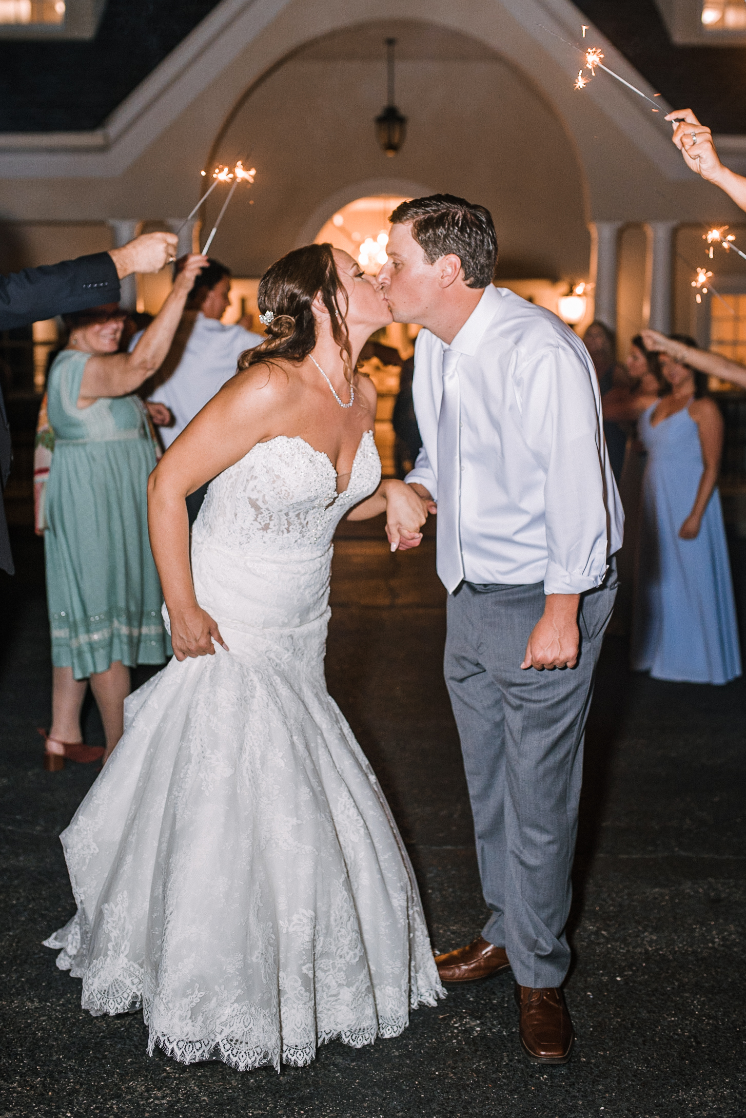 bride and groom kiss under sparkler exit at Evergreen Country Club