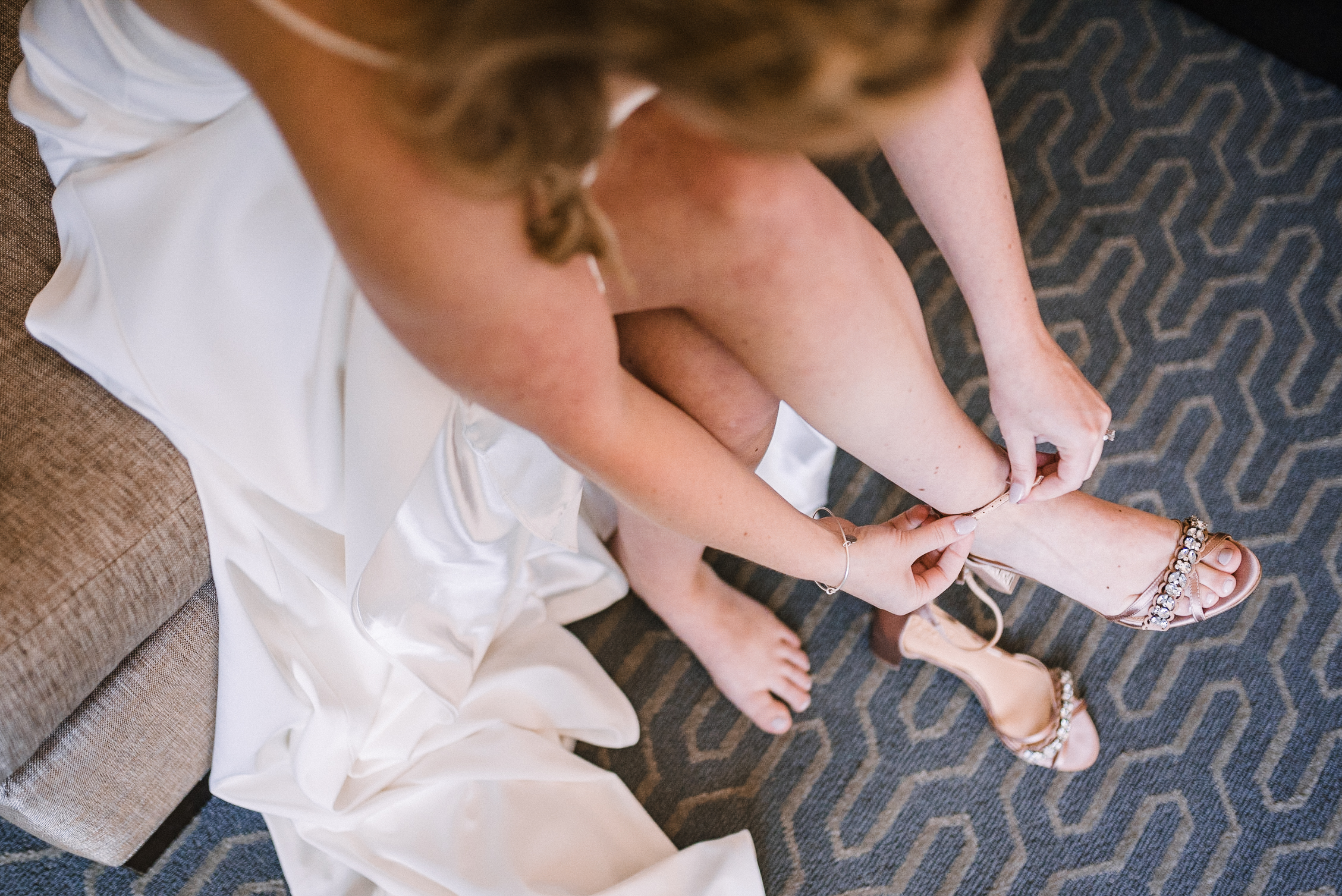 bride putting on her shoes at Embassy Suites in Springfield, VA