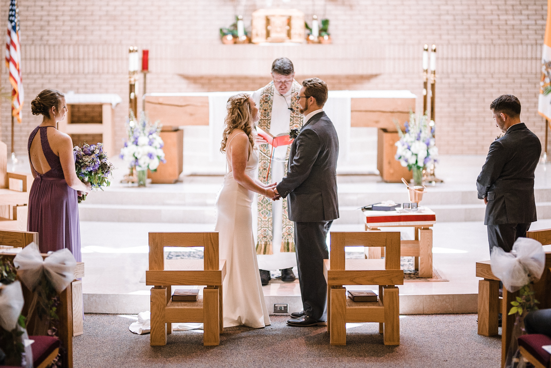 bride and groom holding hands at altar at St. Bernadette Catholic Church