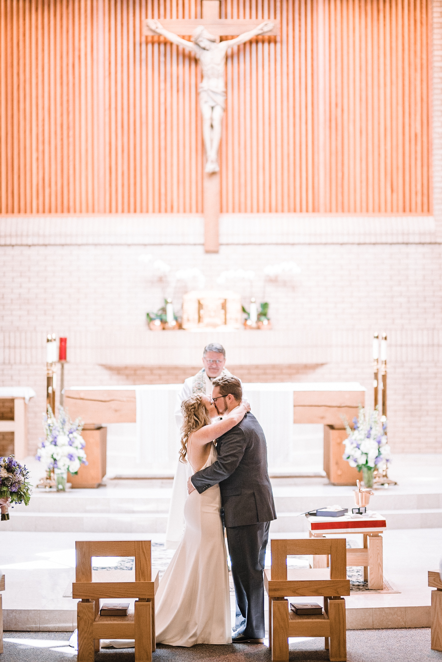 bride and groom kissing at at St. Bernadette Catholic Church