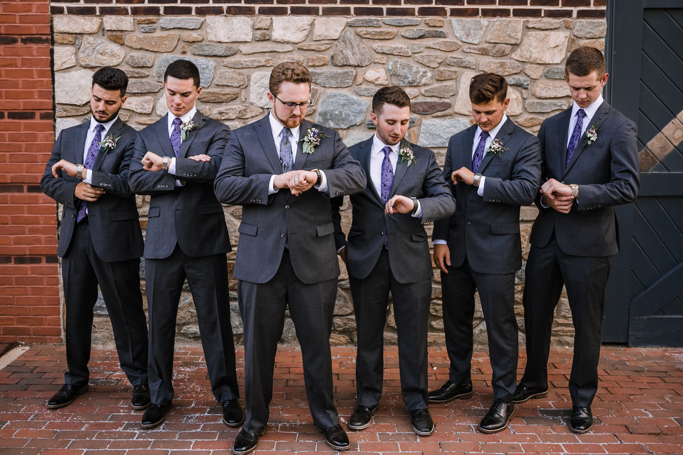 groom and groomsmen looking at their watches at Old Town Alexandria