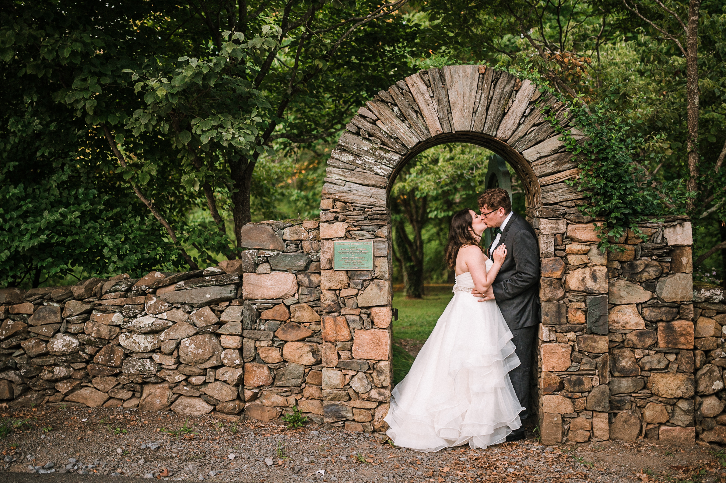 Bride and Groom kissing under arch at Airlie