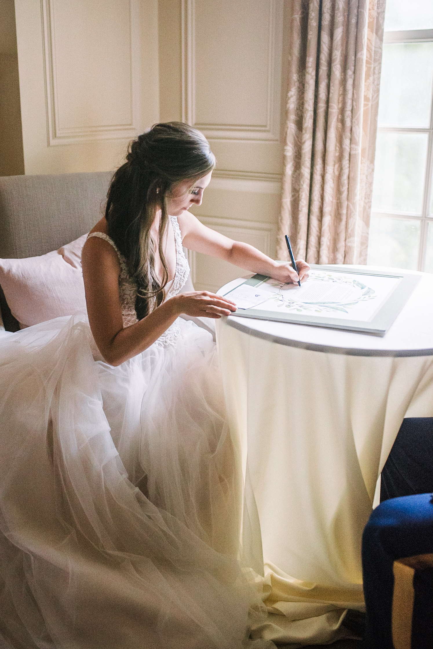 bride signing ketubah at Great Marsh Estate
