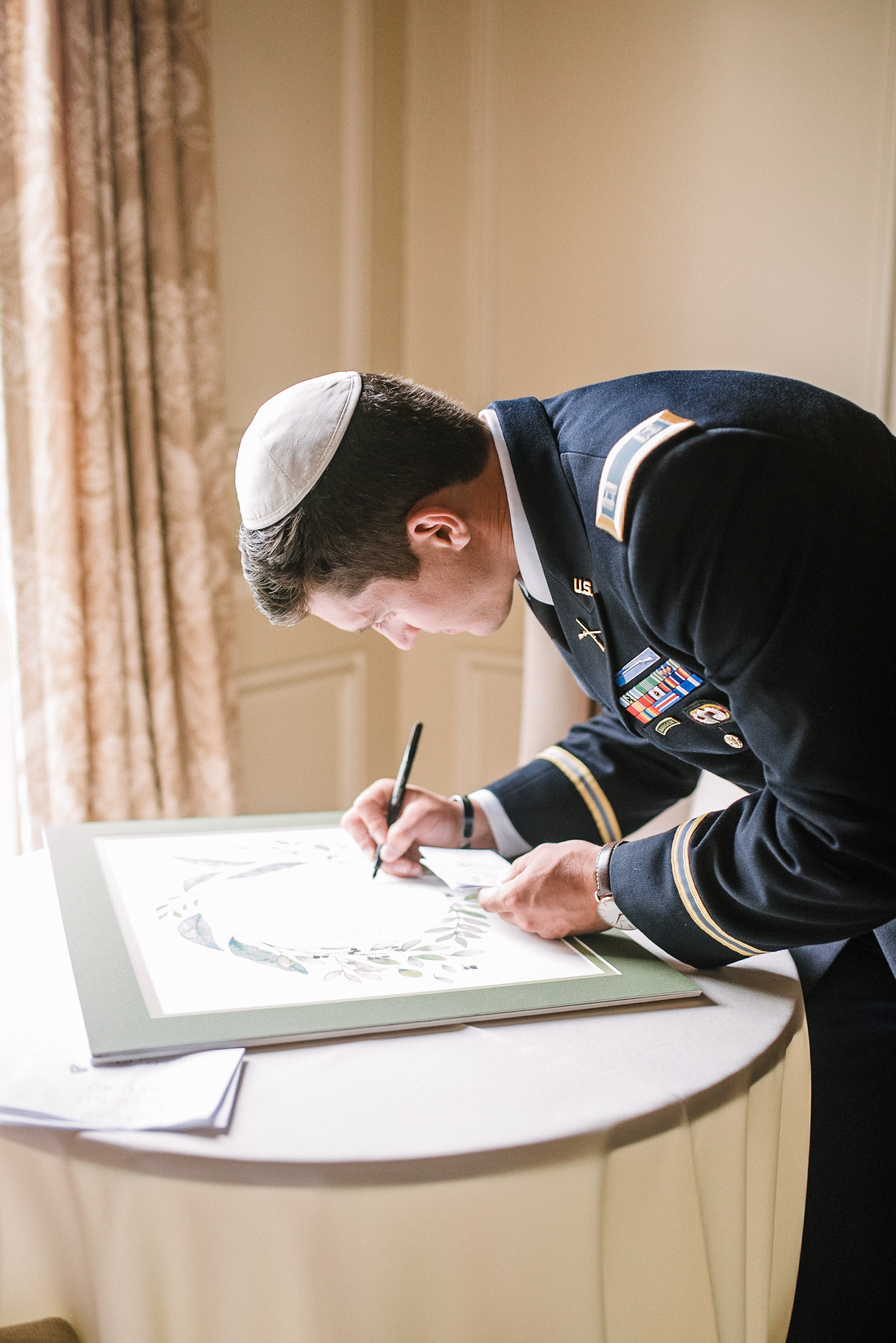groom signing ketubah at Great Marsh Estate