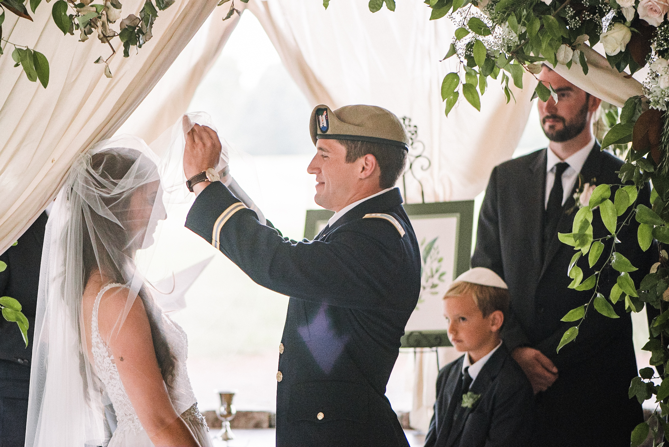 groom pulling back bride's veil at Great Marsh Estate
