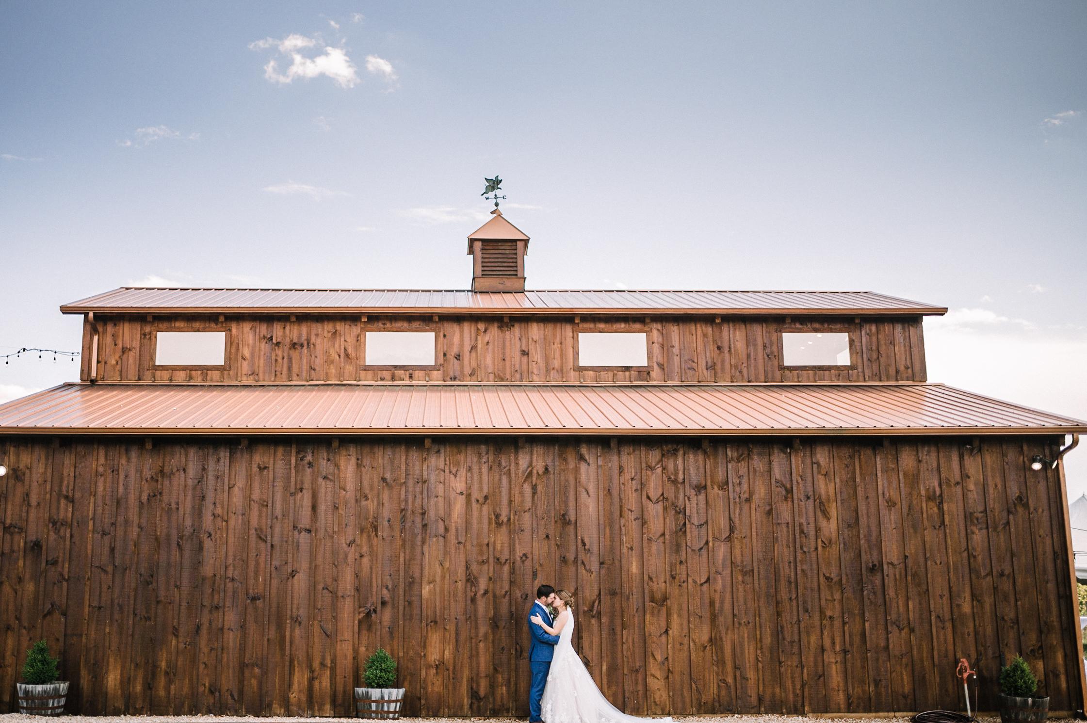 bride and groom kissing at venue at Faithbrooke Barn & Vineyards