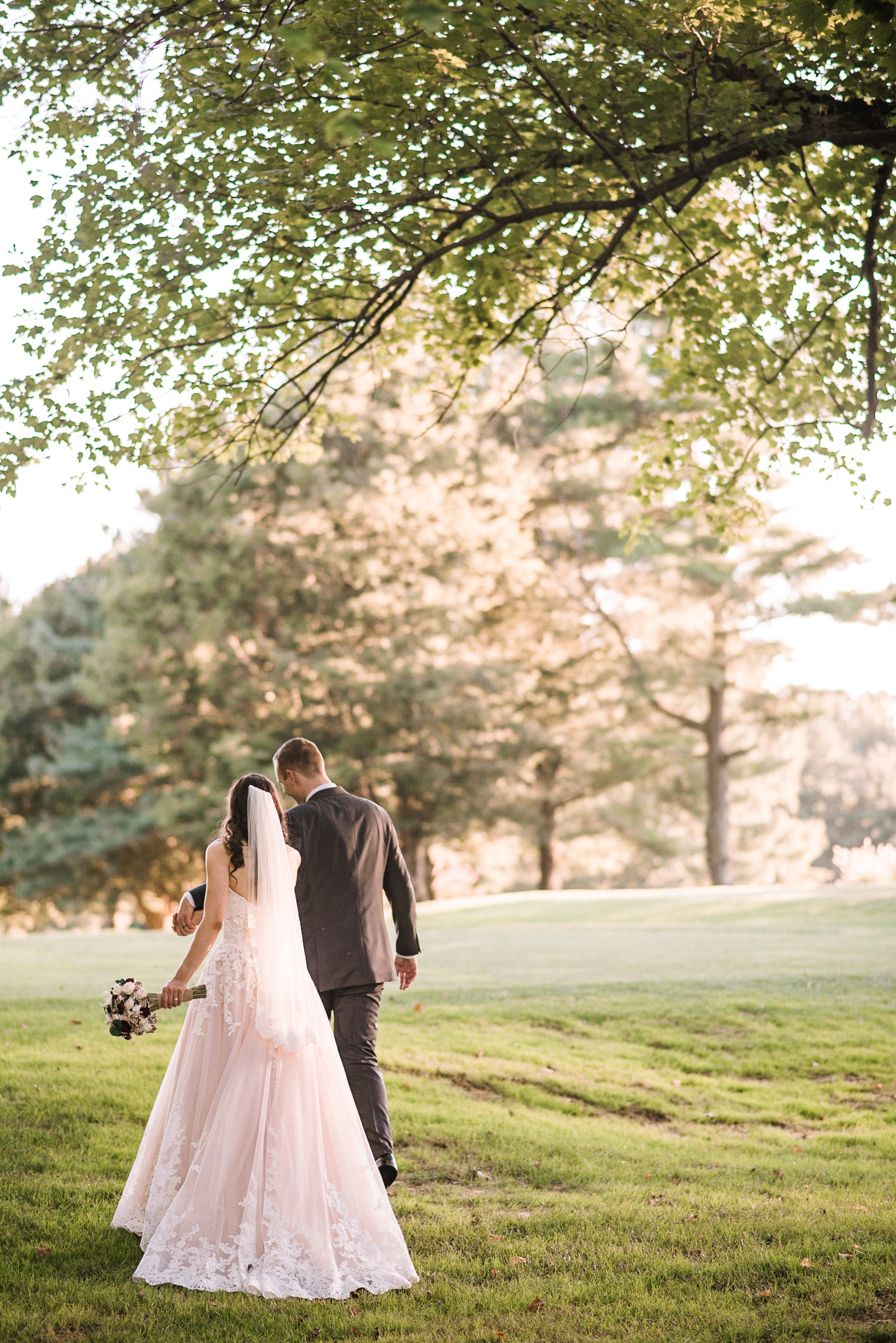 bride and groom holding hands and walking at The Newton White Mansion