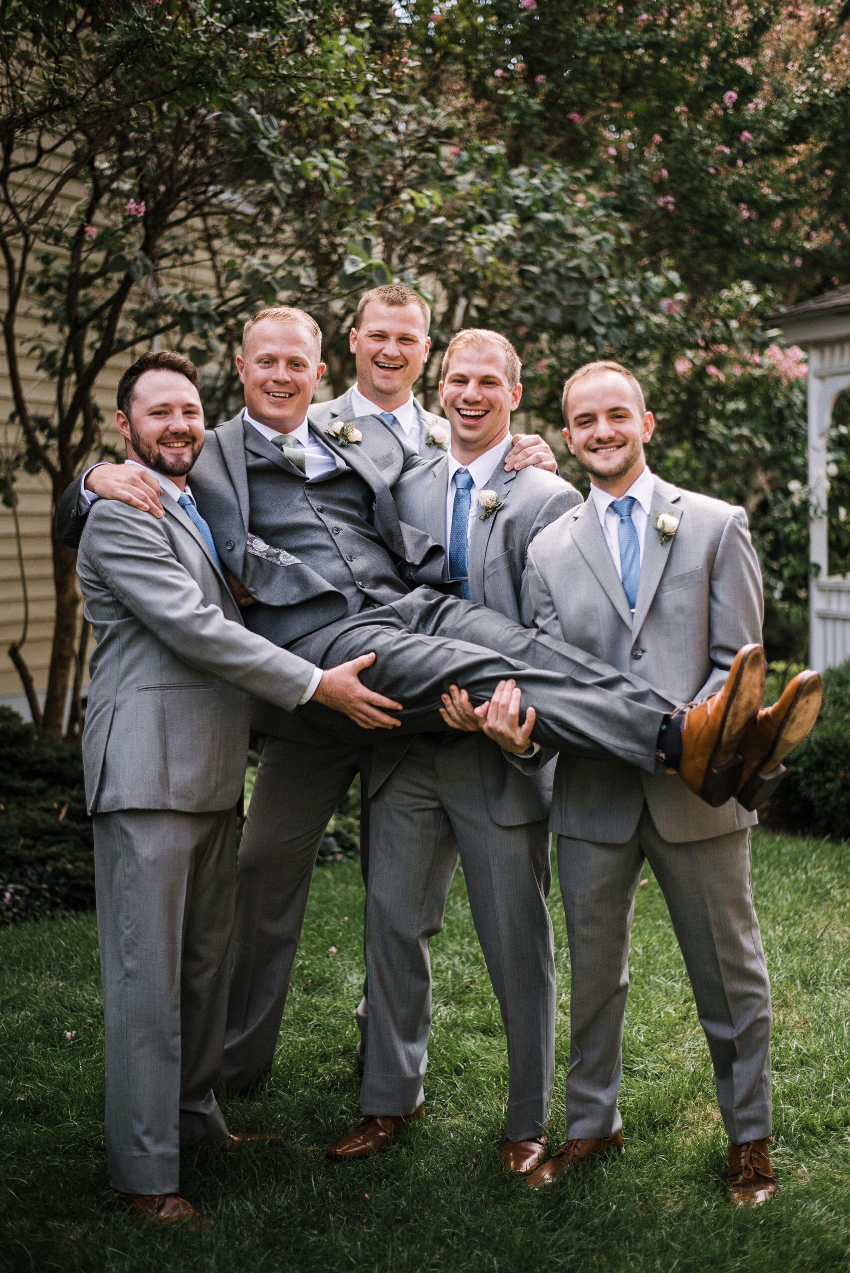 Groomsmen holding groom at Birkby House